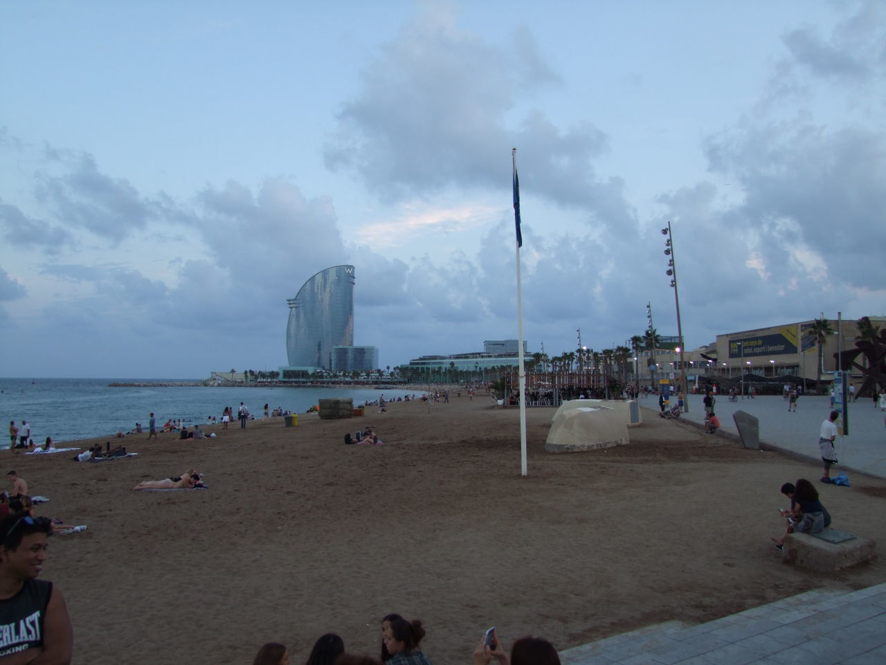 San Sebastia Beach Barcelona Beach Blue Sky And Grey Clouds City Cloudy Sky Coastline Composition Fun Incidental People Outdoor Photography Recreation  San Sebastian Beach Sand Sea Seaside Spaın Tourism Tourist Attraction  Tourist Destination Travel Destinations Vacations Water