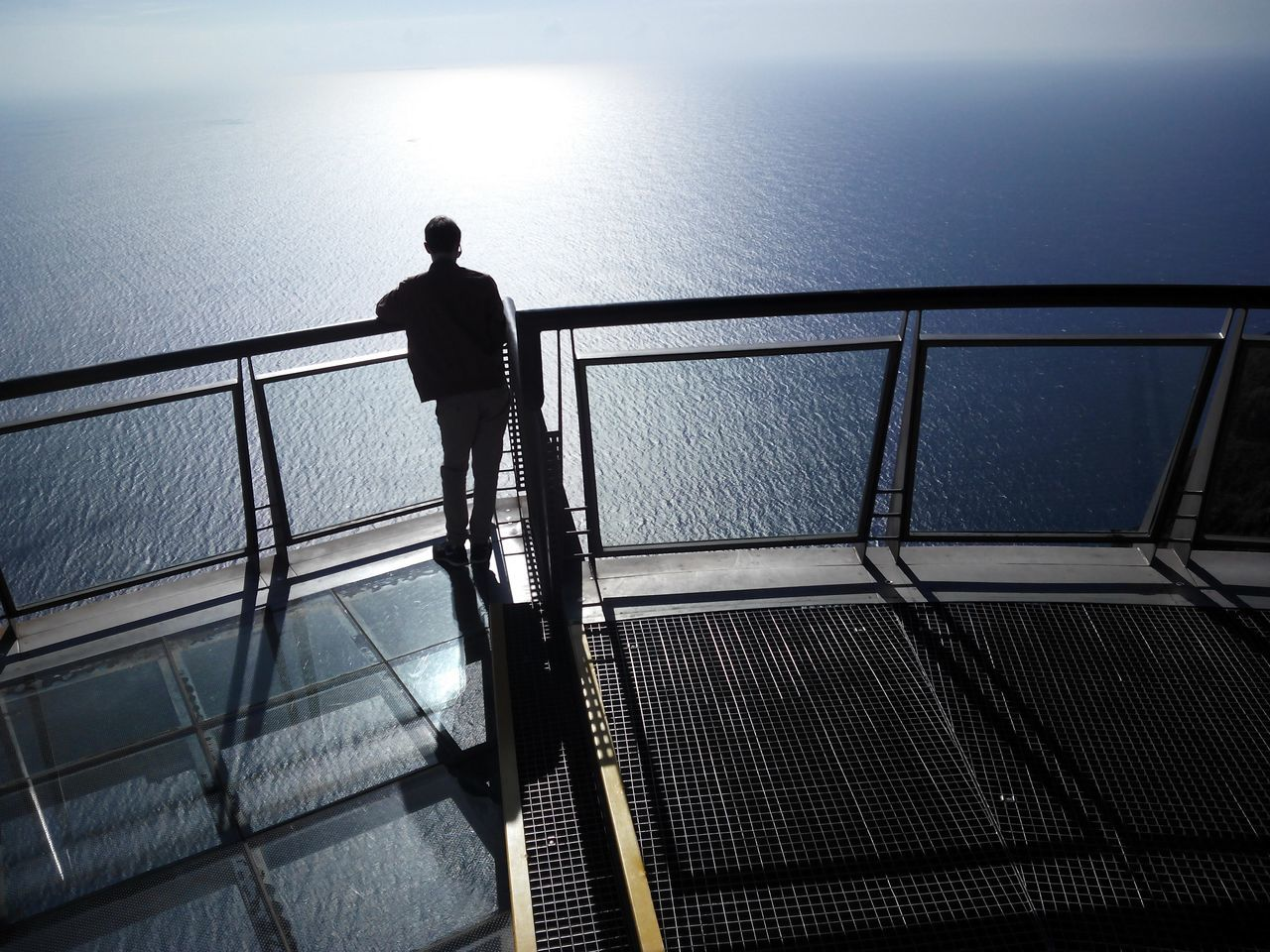 Railing sea water men Rear view Standing solitude Tranquility tranquil scene tourism outdoors day sky Vacations scenics the way forward beauty in Nature Tourist Attraction Tourist Clifftop glass balcony birds eye view Madeira
