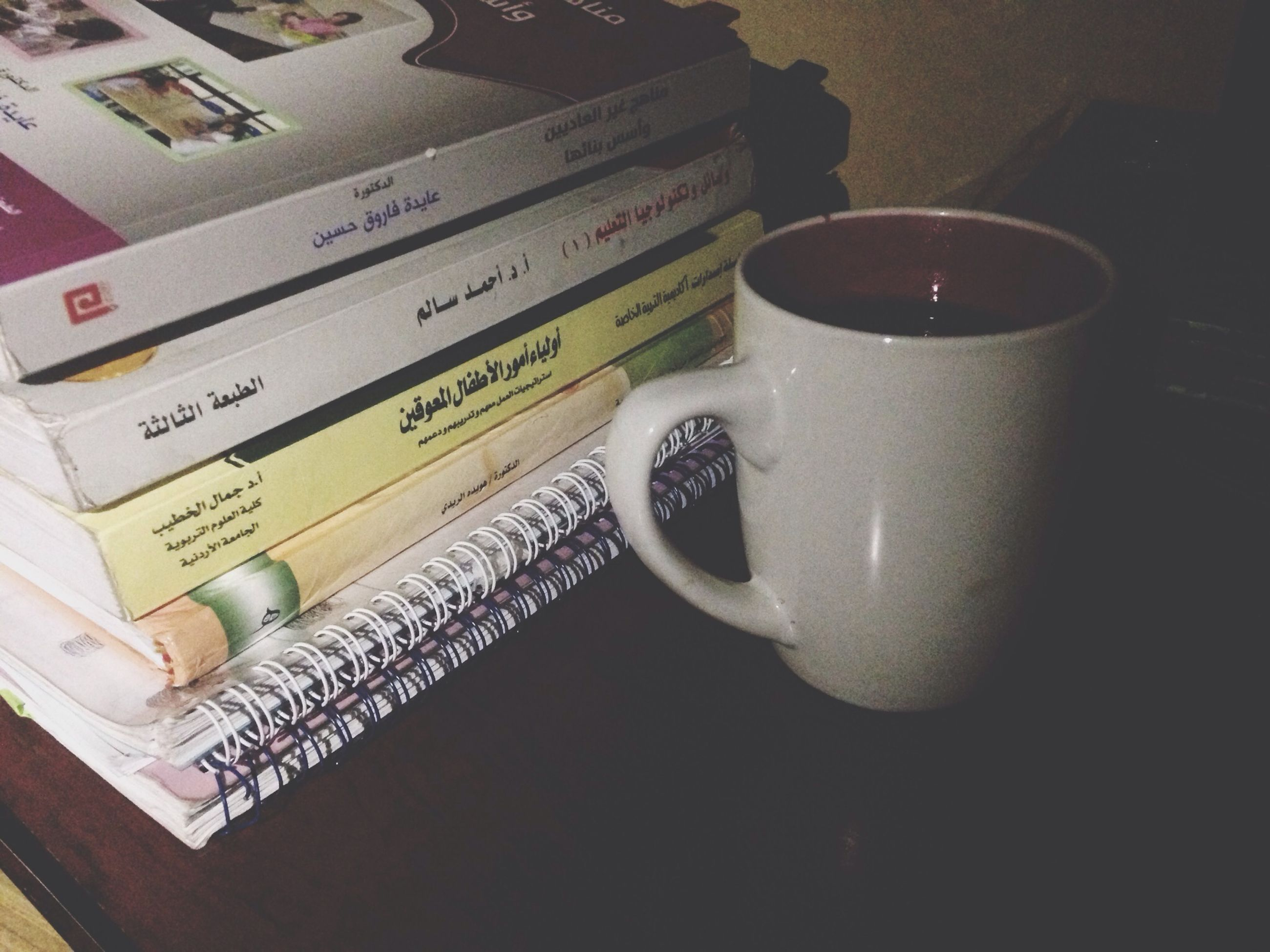 indoors, table, still life, food and drink, text, book, drink, communication, coffee cup, western script, high angle view, close-up, refreshment, paper, freshness, coffee - drink, cup, education, no people, food