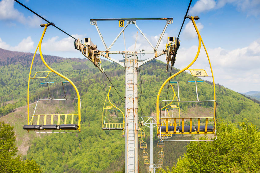 The ski lift with lots of cabins is moving on the background of green mountain nature. Agriculture Day Extream Growth Landscape Manufacturing Equipment Mountain Nature No People Outdoors Rural Scene Scenics Sierra Ski Lift Sky Technology Travel Tree