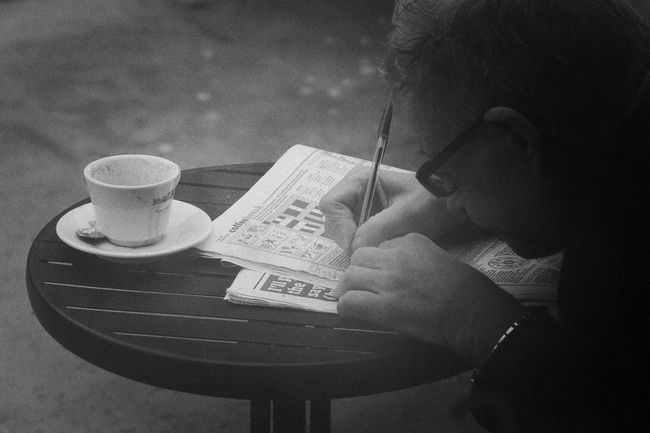 Mand doing Crossword with Coffee Cup Book Detail Documentary Nature Photography Photography Taking Photos A Education Full Frame High Angle View Hobbies Holding Home Human Body Part Indoors  Man Doing Crossword Outside Cafe South London Music Occupation One Person Paper Part Of Pattern Pen Reading Reportage Street Photos Taking Fotos Images Photographic Camera Lens Architectural Design Building Structual Support Detail Of Tower Block In Sunshine Blue Sk Table Technology