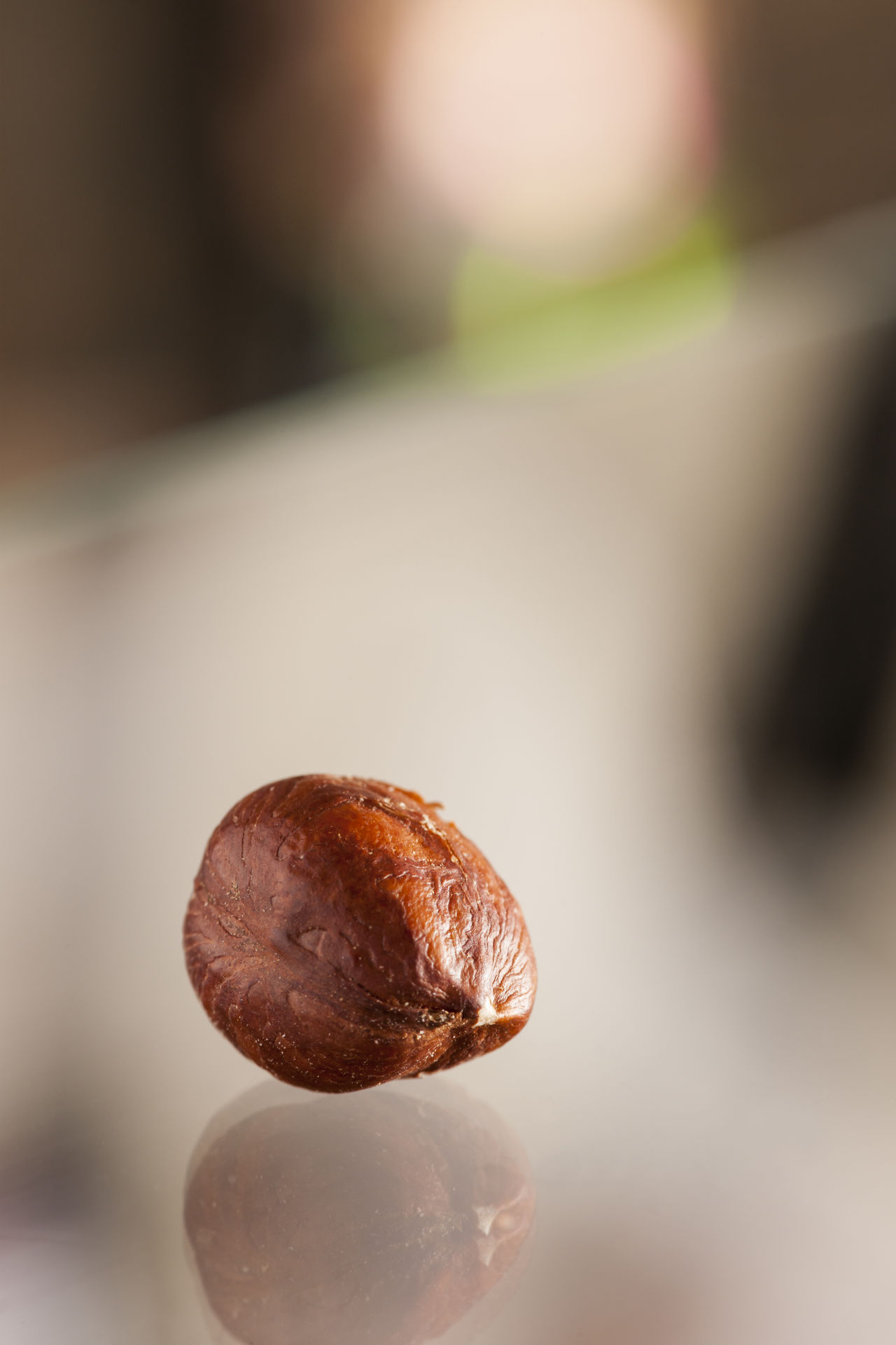 Single hazelnut on a glass plate with blurred mirrors of the surroundings. Brown Close-up Day Focus On Foreground Food Food And Drink Freshness Glass Plate Hazelnut Nature No People Nut Nut - Food Outdoors Reflection