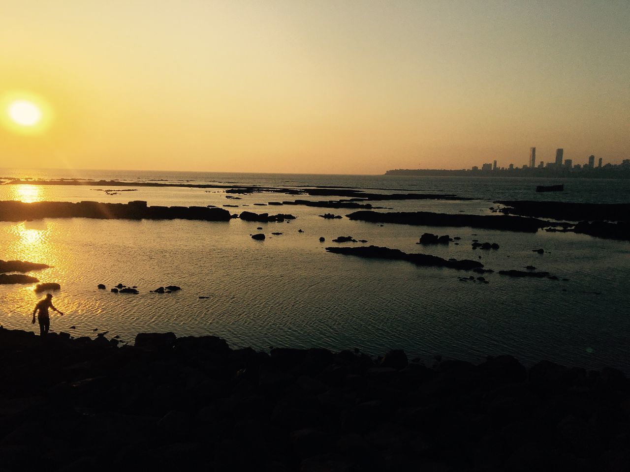 sunset, water, reflection, silhouette, sea, nature, scenics, beauty in nature, sky, outdoors, tranquility, sun, tranquil scene, travel destinations, beach, clear sky, no people, horizon over water, building exterior, architecture, city, day
