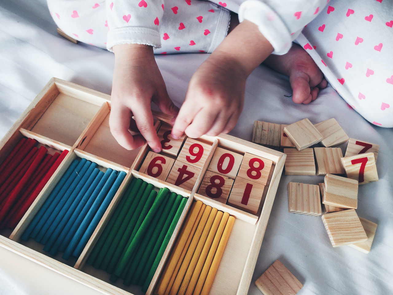 High Angle View Of Child Arranging Blocks With Number In Box On Bed
