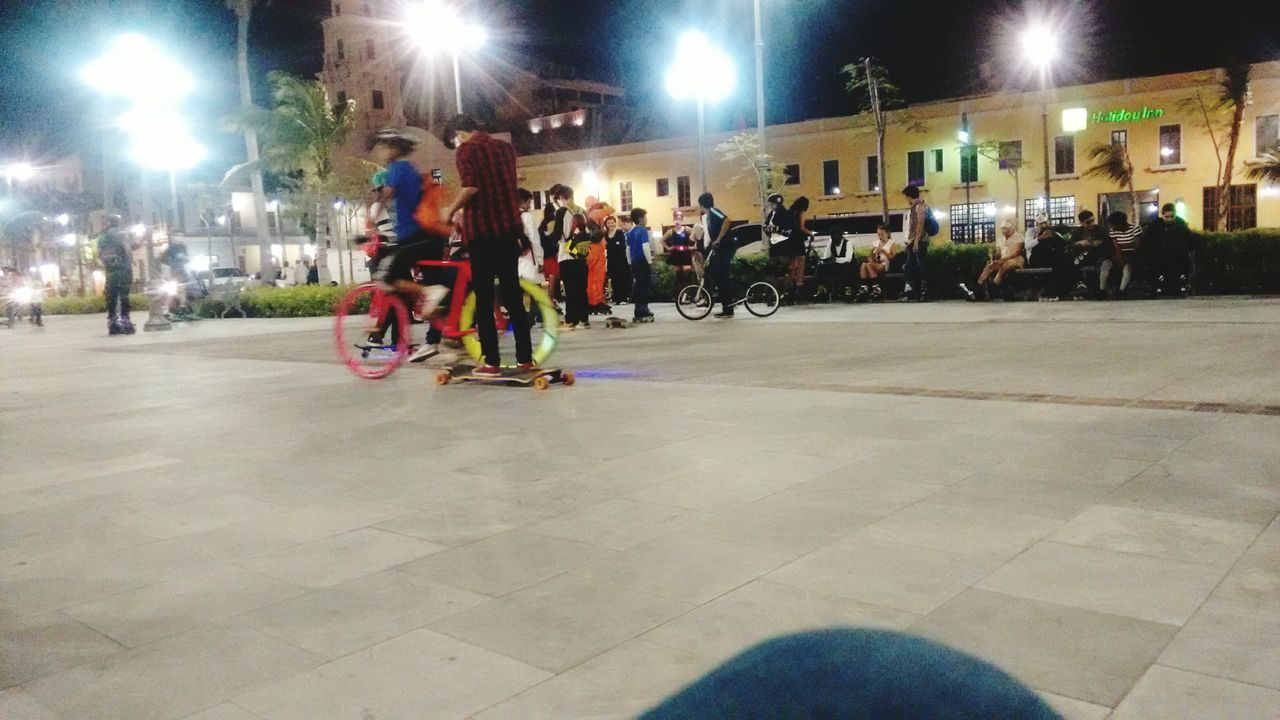 large group of people, illuminated, real people, sport, lifestyles, night, leisure activity, bicycle, men, transportation, built structure, exercising, women, outdoors, competition, people