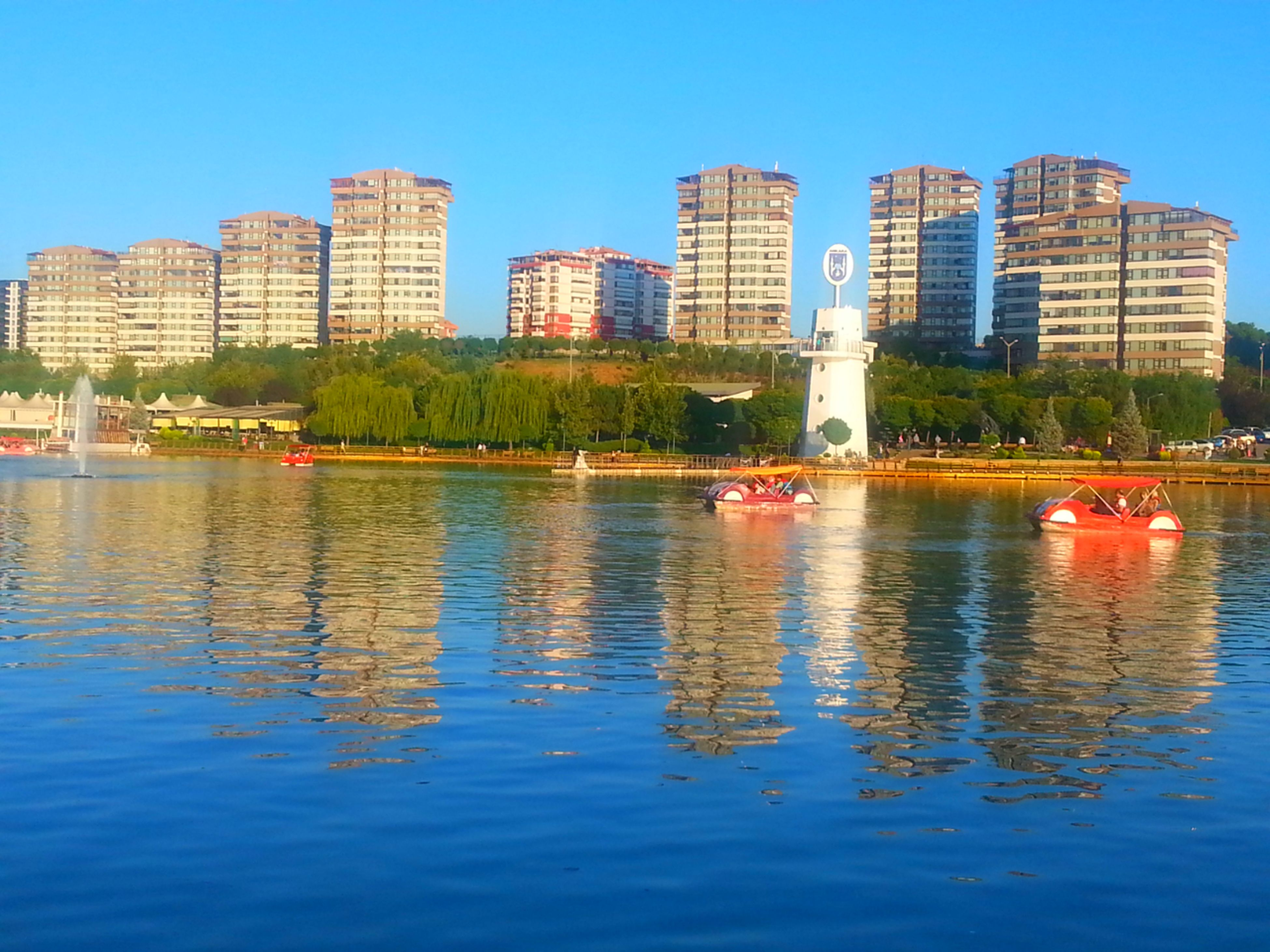 building exterior, architecture, water, built structure, waterfront, city, clear sky, river, nautical vessel, reflection, skyscraper, tree, blue, boat, transportation, tower, rippled, lake, urban skyline, office building