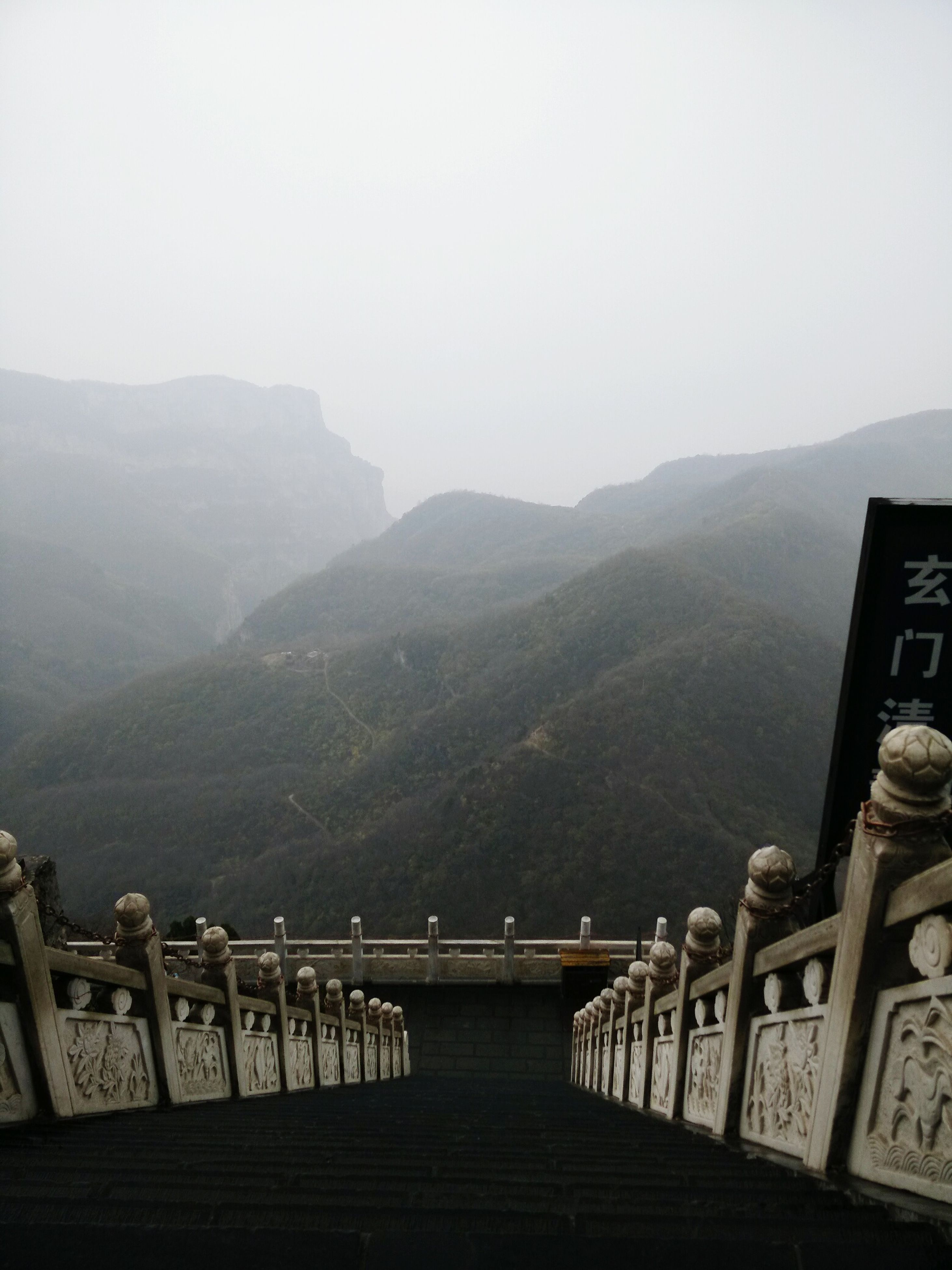 mountain, mountain range, railing, fog, scenics, tranquility, tranquil scene, built structure, beauty in nature, architecture, copy space, nature, sky, observation point, foggy, day, water, landscape, idyllic