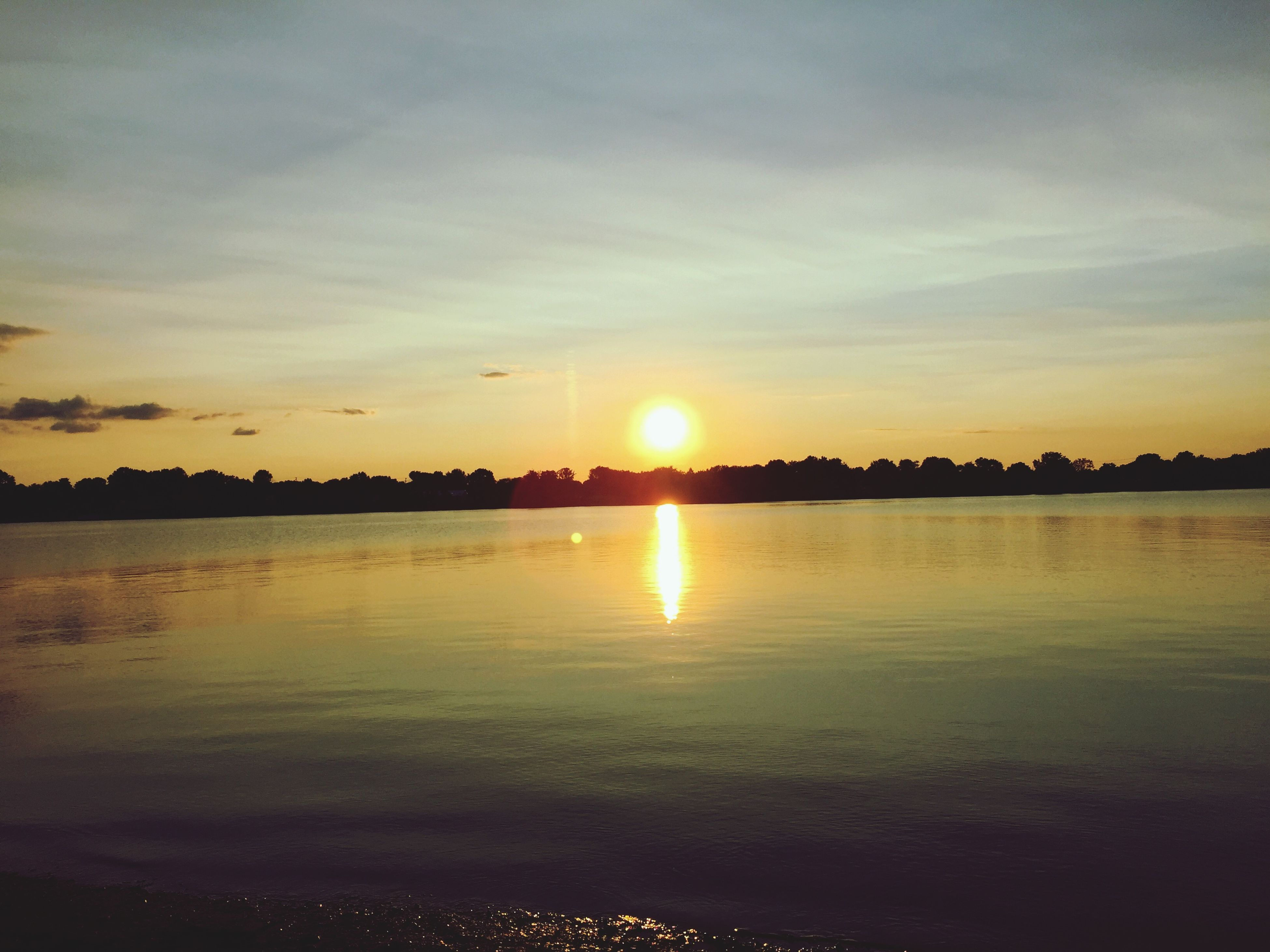 sunset, sun, water, scenics, tranquil scene, reflection, beauty in nature, tranquility, orange color, sky, silhouette, idyllic, nature, sunlight, waterfront, lake, sea, cloud - sky, outdoors, sunbeam