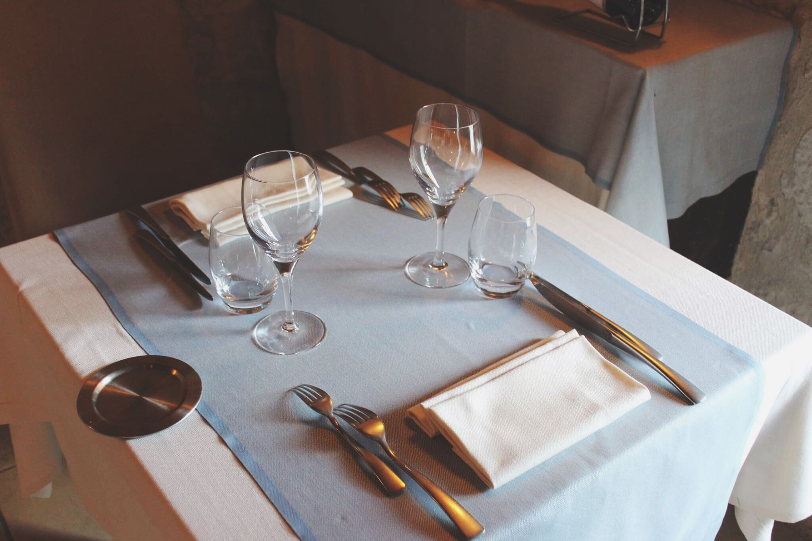 wineglass, table, drinking glass, napkin, place setting, restaurant, plate, table knife, high angle view, empty, wine, fork, food and drink, no people, cutlery, elegance, dining table, drink, tablecloth, wood - material, indoors, water, day, close-up