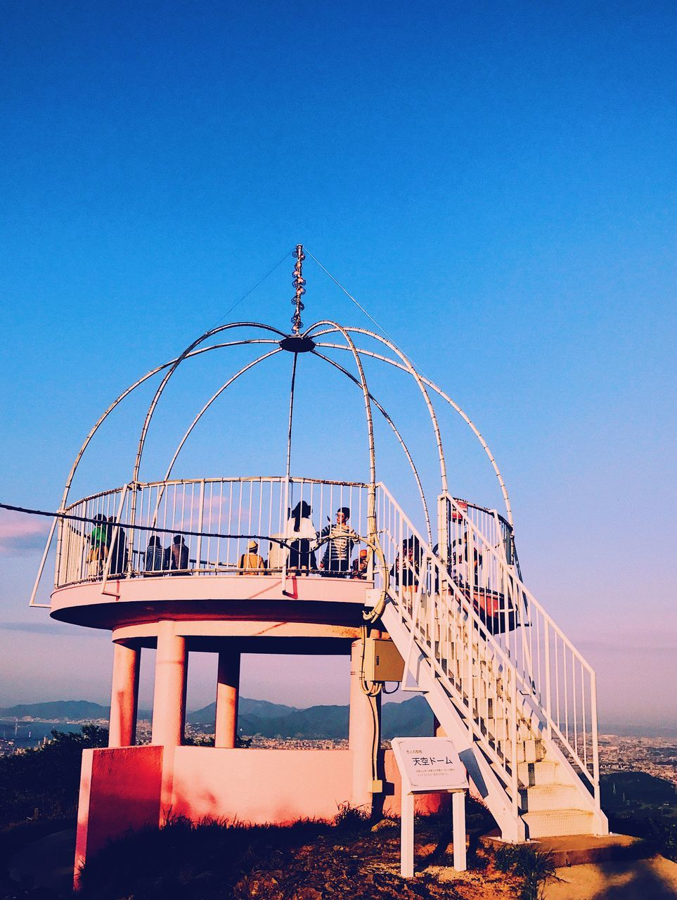 People On Lookout Tower Against Clear Blue Sky