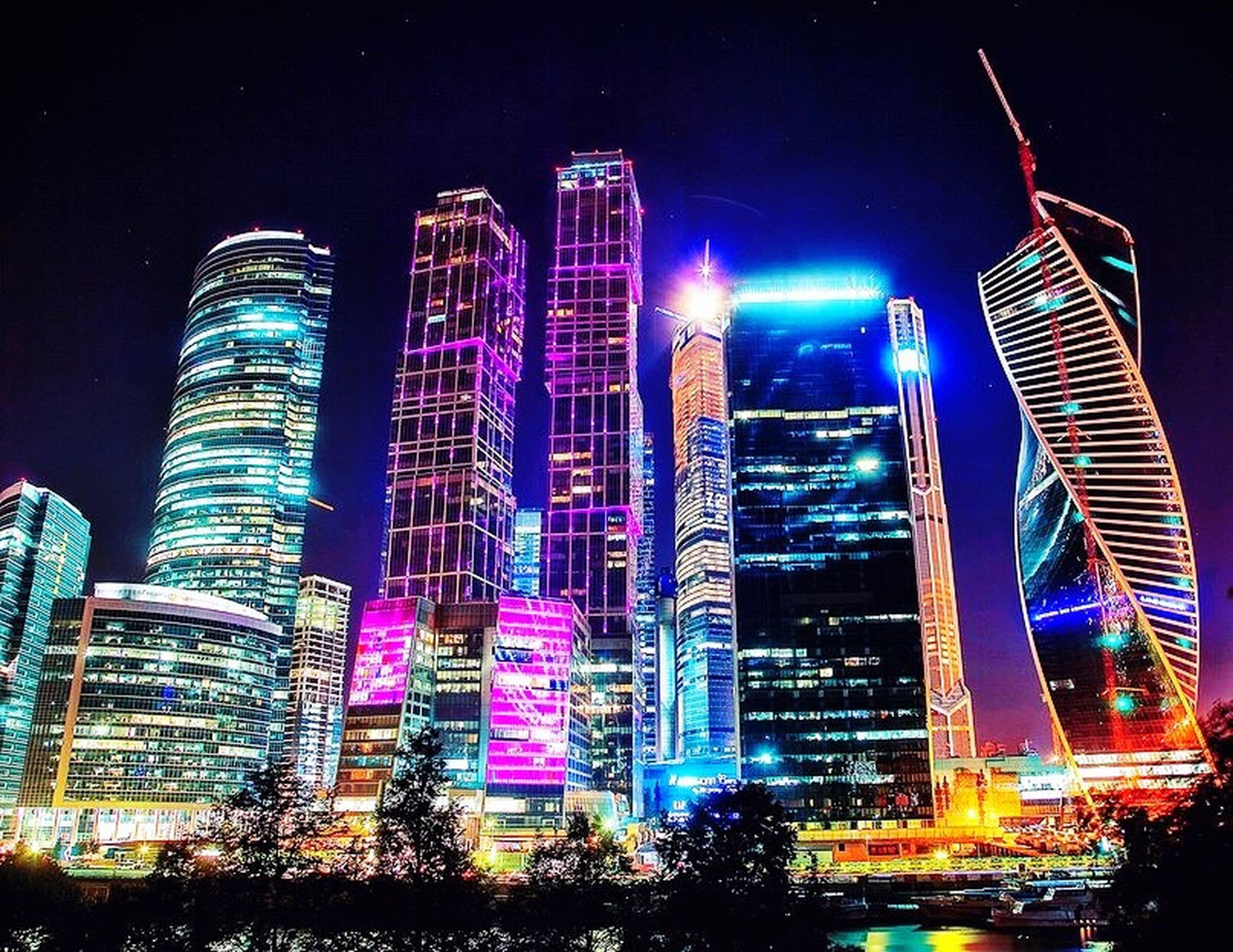 illuminated, night, building exterior, architecture, city, skyscraper, built structure, modern, tall - high, tower, office building, cityscape, capital cities, travel destinations, low angle view, financial district, famous place, sky, city life, travel