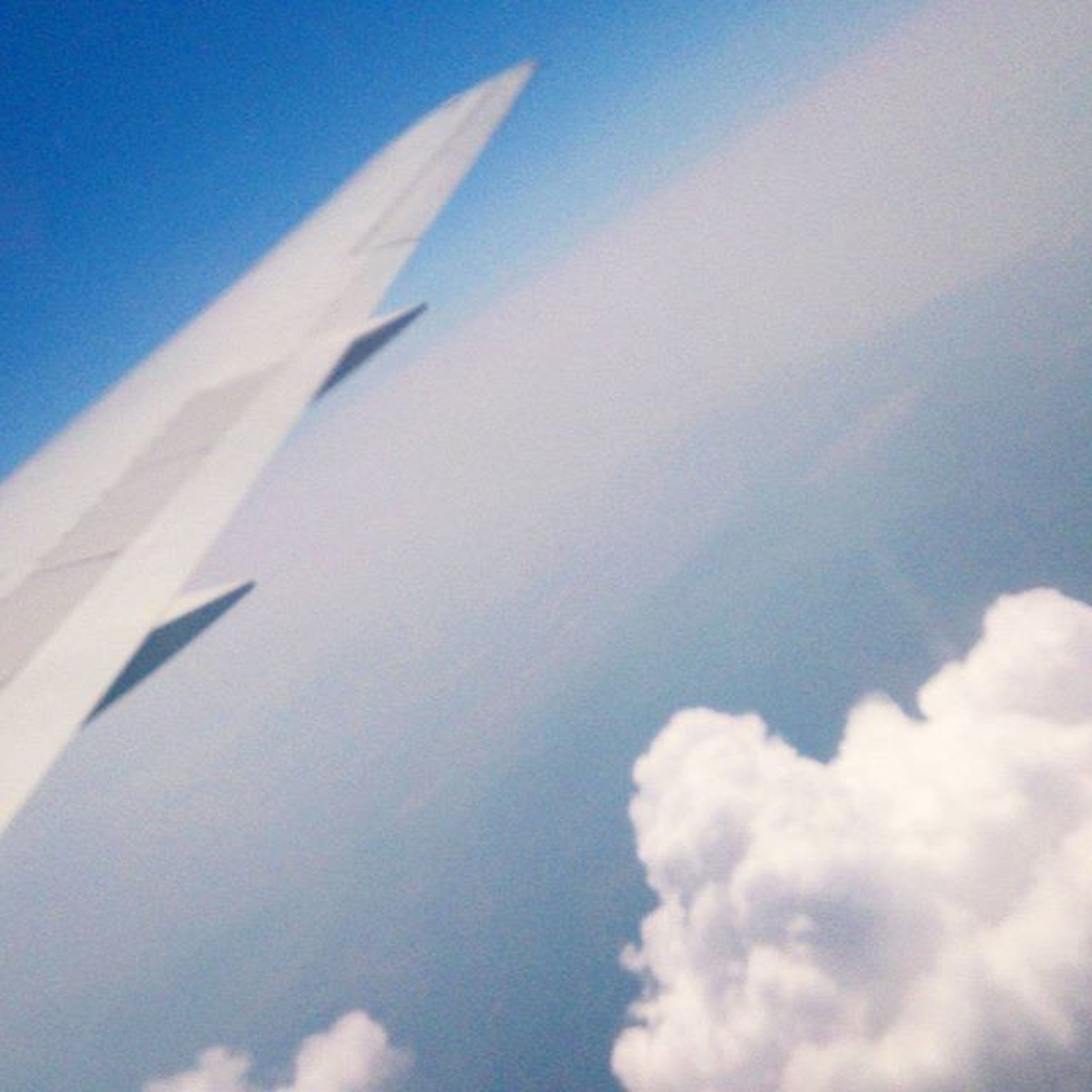 low angle view, airplane, blue, sky, air vehicle, flying, part of, transportation, cloud - sky, vapor trail, cropped, aircraft wing, nature, day, no people, outdoors, cloud, mode of transport, white color, beauty in nature