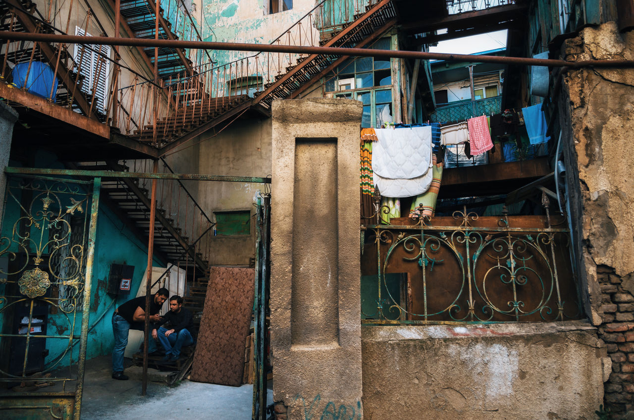 Colorful Tbilisi courtyard in the Old City, Georgia Adults Only Architecture Building Exterior Built Structure Clothes Colorful Courtyard  Drying Clothes Georgia Hanging House Landmark Only Men Outdoor Photography Outdoors Real People Staircase Steet Photography Street Street Photography Streetphotography Tbilisi