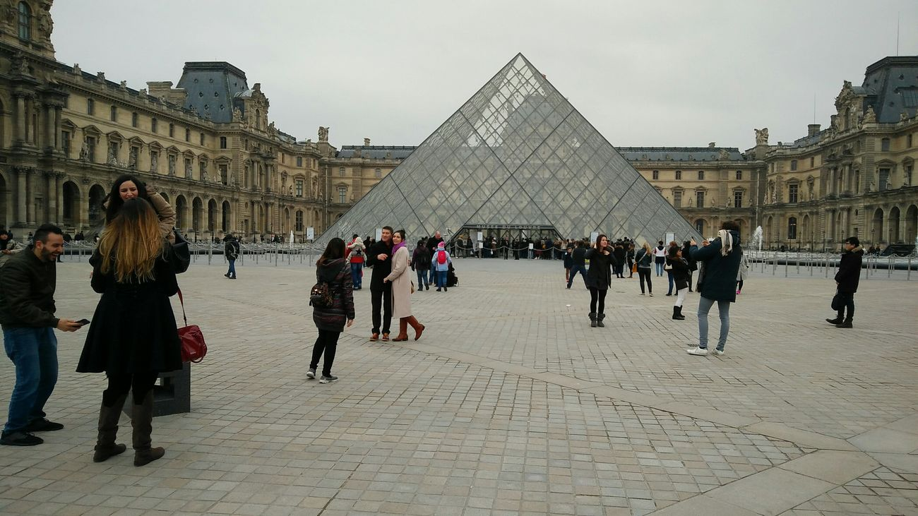 Taking Photos at the Louvre. · Paris France Louvre Museum Louvre Pyramid Photos Posing People Crowd Tourism Landmark Monument Culture Art History Architecture Travel Destinations Outdoors Gray Sky Cloudy Day