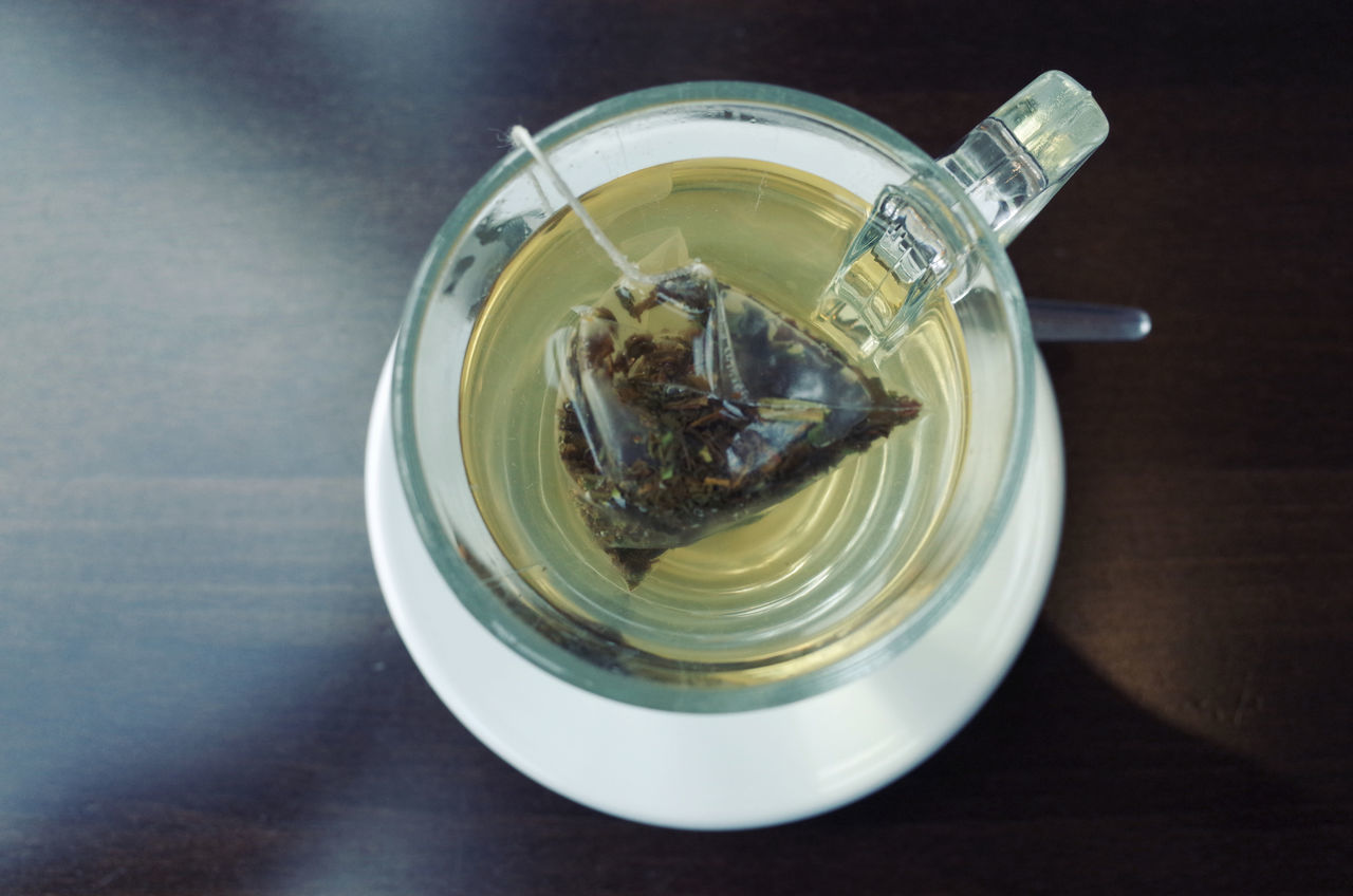 High Angle View Of Green Tea Bag In Cup Of Water On Table