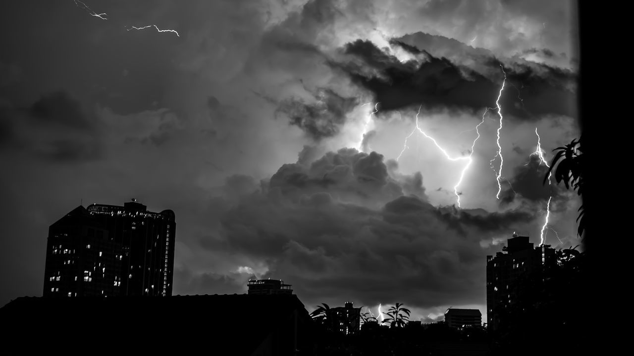 Low Angle View Of Lightning Over Cityscape Against Dramatic Sky