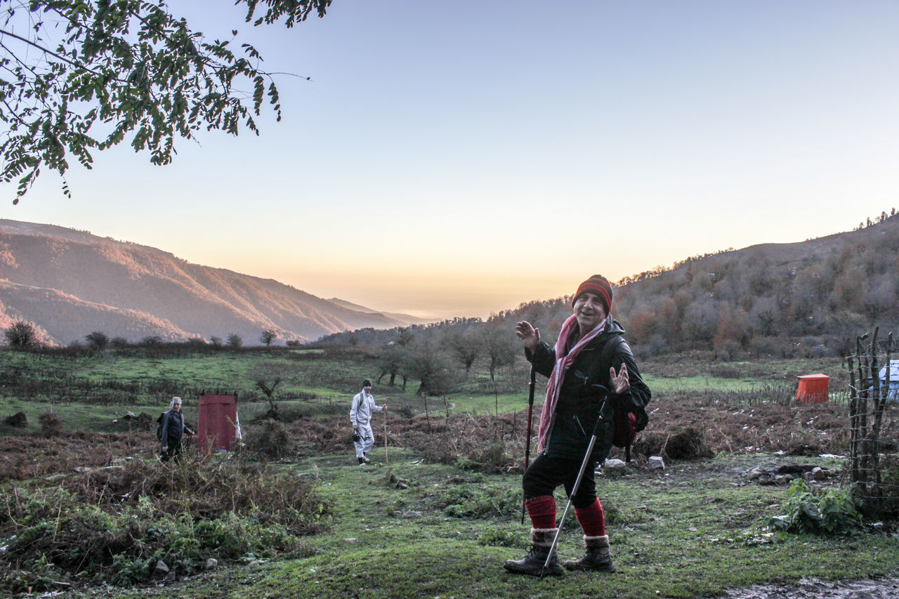 field, real people, mountain, men, nature, grass, medium group of people, full length, clear sky, sky, landscape, outdoors, sunset, women, beauty in nature, standing, tree, day, adult, people