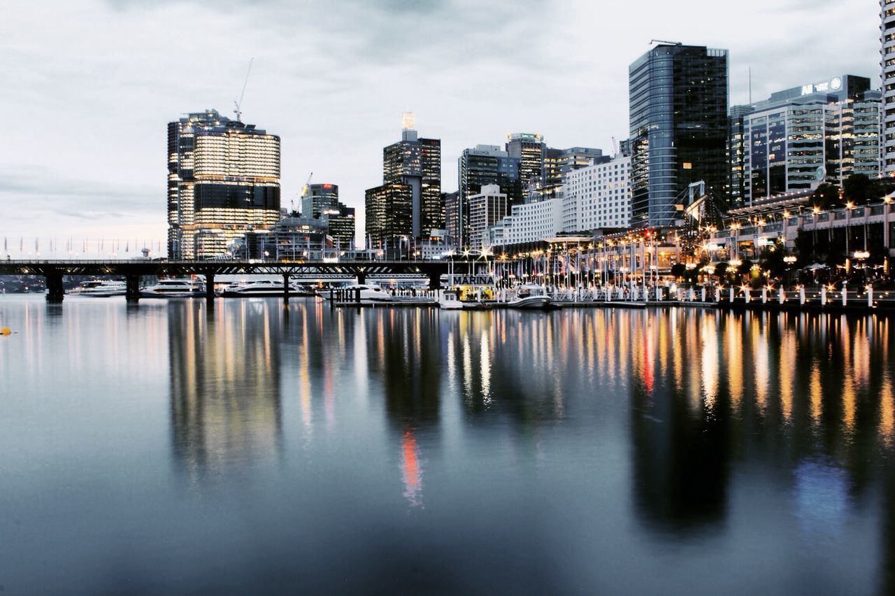 Exploring Sydney city before sunset. Water Architecture Built Structure Building Exterior Waterfront City Reflection Mid Distance River Sea Tall Illuminated Skyscraper Sky Cloud Calm Development Building Story Water Surface Ocean Exploring First Eyeem Photo Myfavoriteplace My Favorite Place