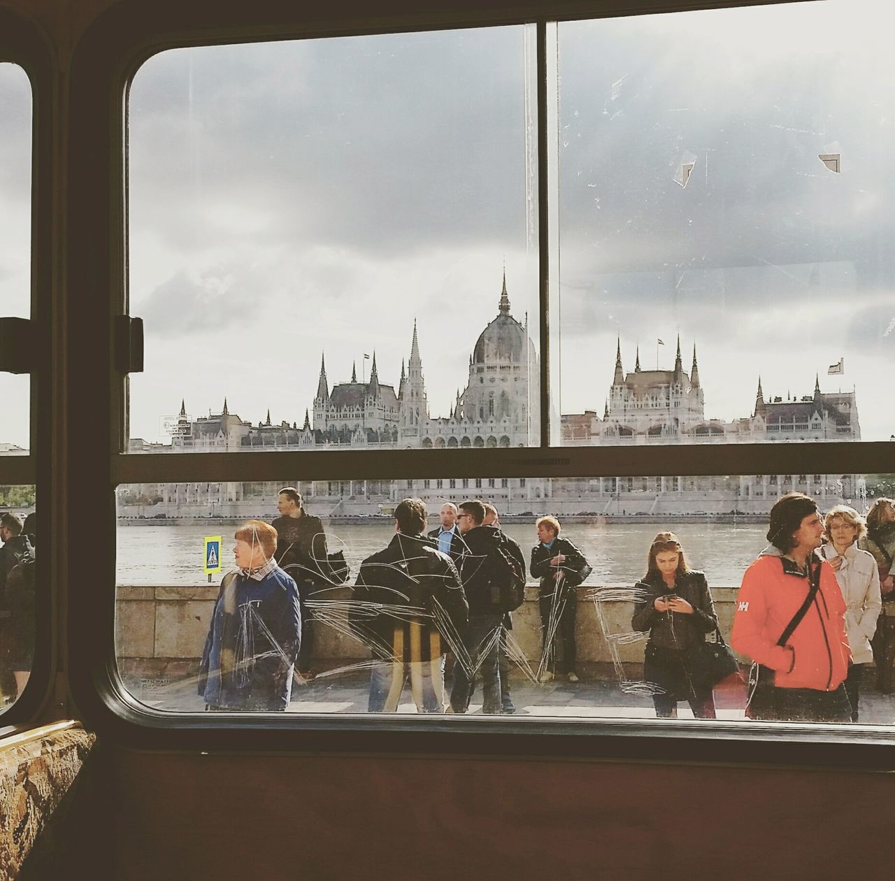 architecture, built structure, building exterior, travel destinations, travel, water, transportation, real people, tourism, city, sky, window, men, mode of transport, cloud - sky, river, day, communication, dome, land vehicle, lifestyles, women, indoors, cityscape, chain bridge, people