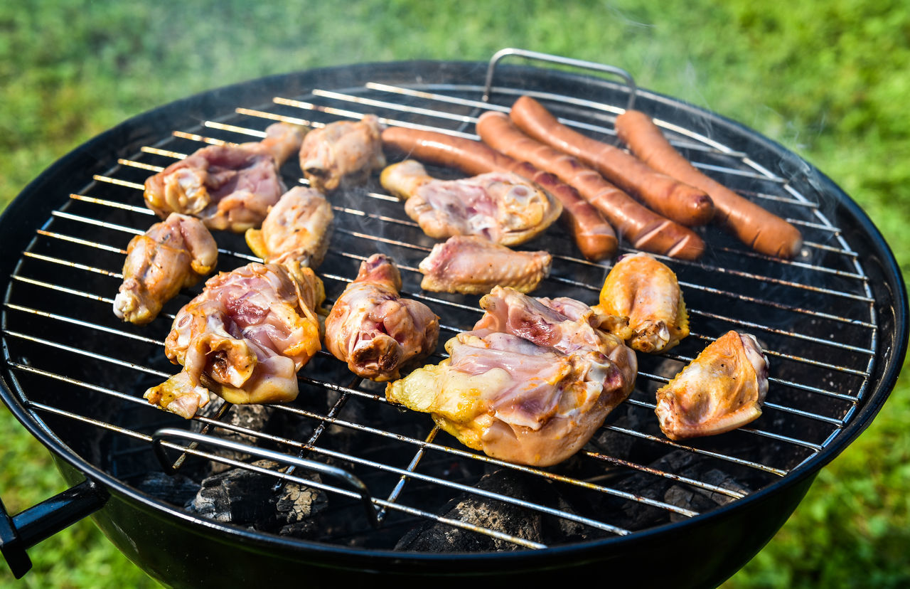 Delicious variety of meat on barbecue grill with char coal. Grilling food on a weber type small cheap BBQ grill at home. Sausages, chicken, and hot dogs in nature. Backgrounds Barbecue Barbecue Grill BBQ Cevapcici Chic Coal Day Food Freshness Grass Grilled Heat - Temperature Hot Making Music Meat Outdoors Picknik Preparing Food Sausage Stem Summer Sunset Wing Wings