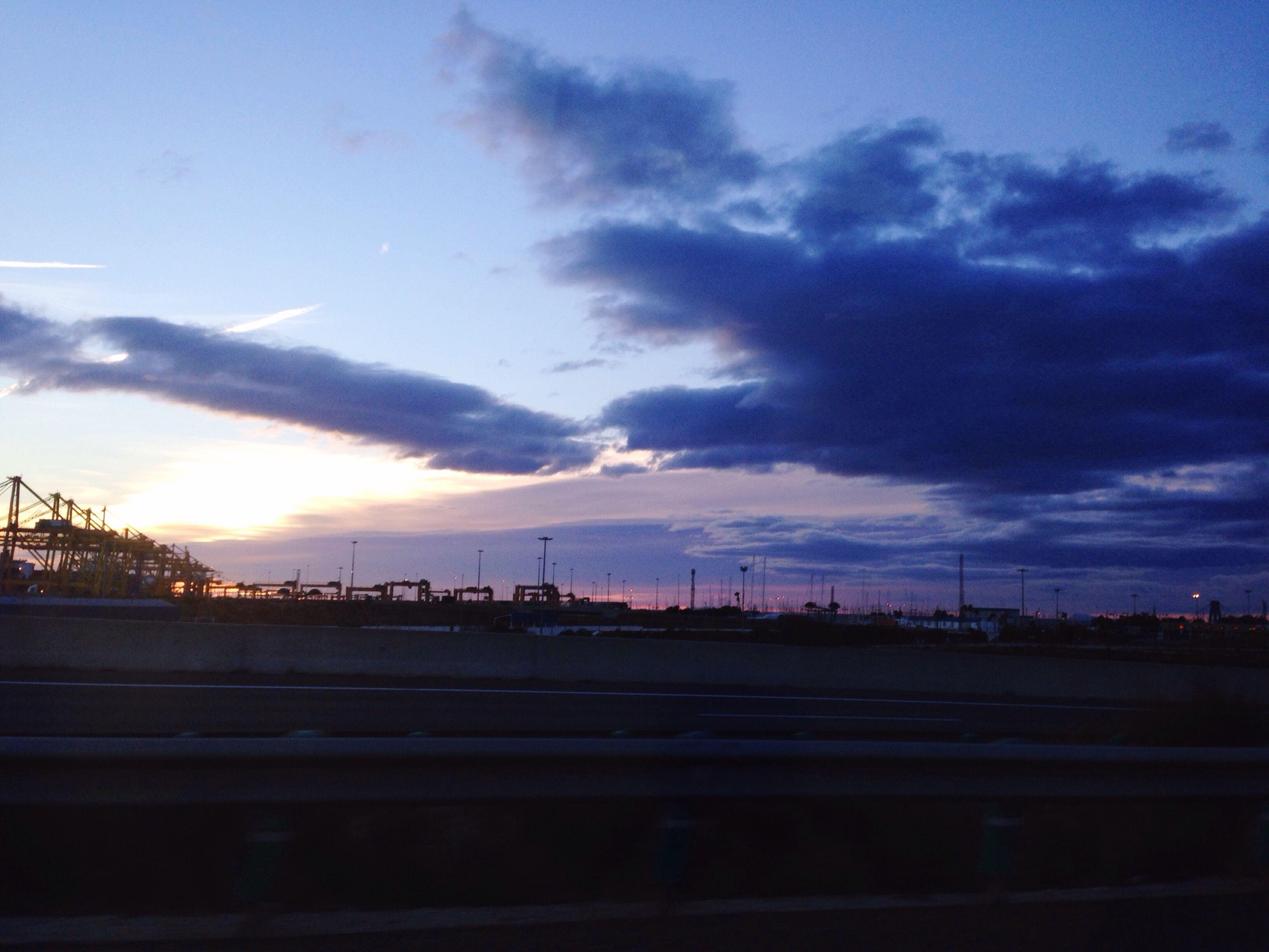 sky, cloud - sky, building exterior, built structure, architecture, city, sunset, dusk, silhouette, cloudy, cloud, railroad track, transportation, connection, railing, crane - construction machinery, outdoors, no people, blue, rail transportation