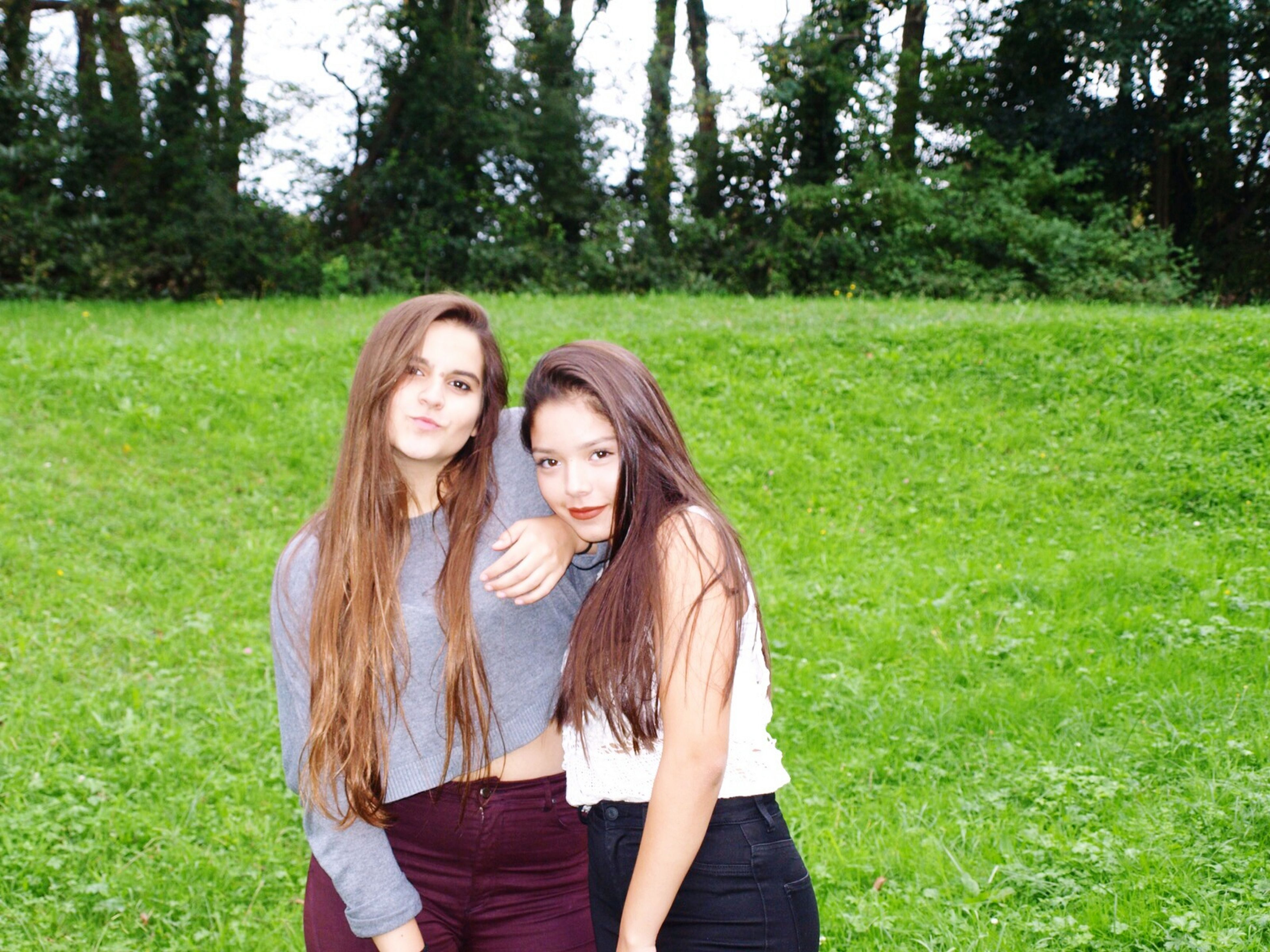 person, young adult, young women, lifestyles, grass, smiling, looking at camera, portrait, leisure activity, casual clothing, long hair, tree, front view, happiness, field, three quarter length, standing