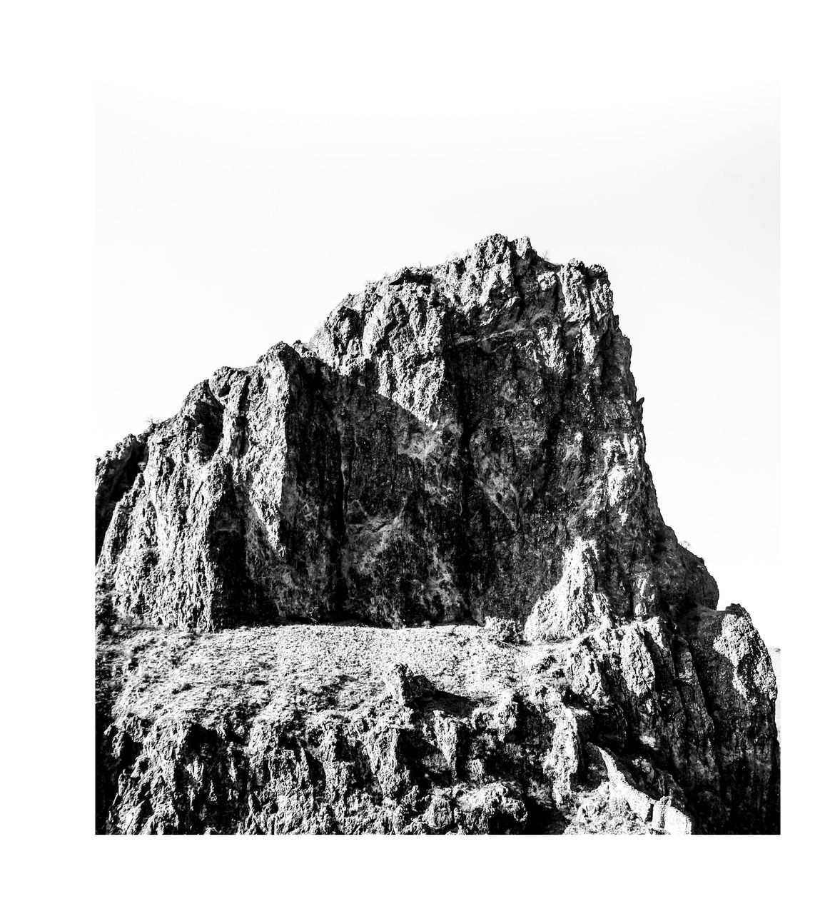 rock - object, rock formation, rock, rough, clear sky, nature, cliff, mountain, no people, textured, outdoors, scenics, day, beauty in nature, sky, white background, sea