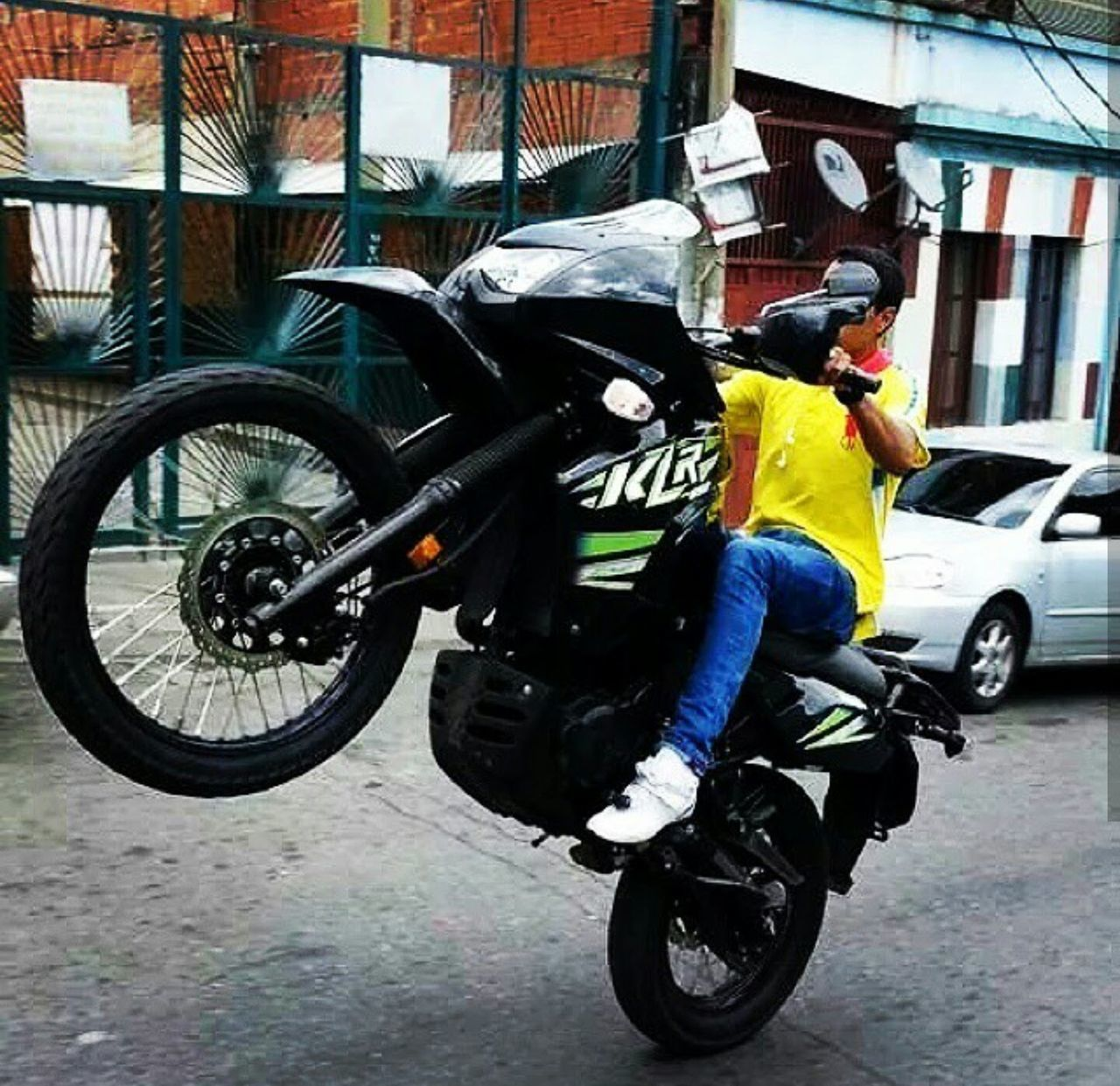 helmet, transportation, mode of transport, land vehicle, real people, one person, full length, motorcycle, headwear, men, crash helmet, riding, day, built structure, outdoors, sports helmet, one man only, architecture, building exterior, biker, only men, adult, people