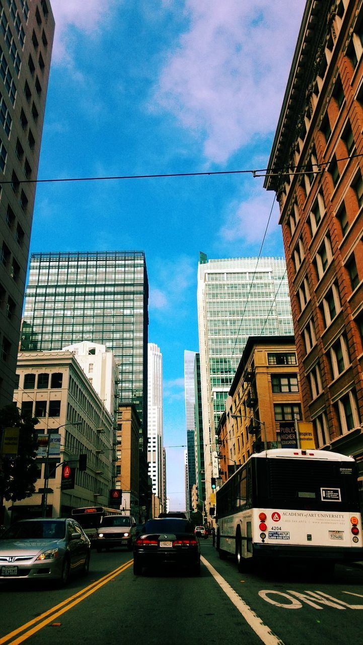architecture, building exterior, built structure, car, city, transportation, land vehicle, mode of transport, day, road, skyscraper, sky, street, cloud - sky, city life, outdoors, tall, travel destinations, no people, modern, cityscape