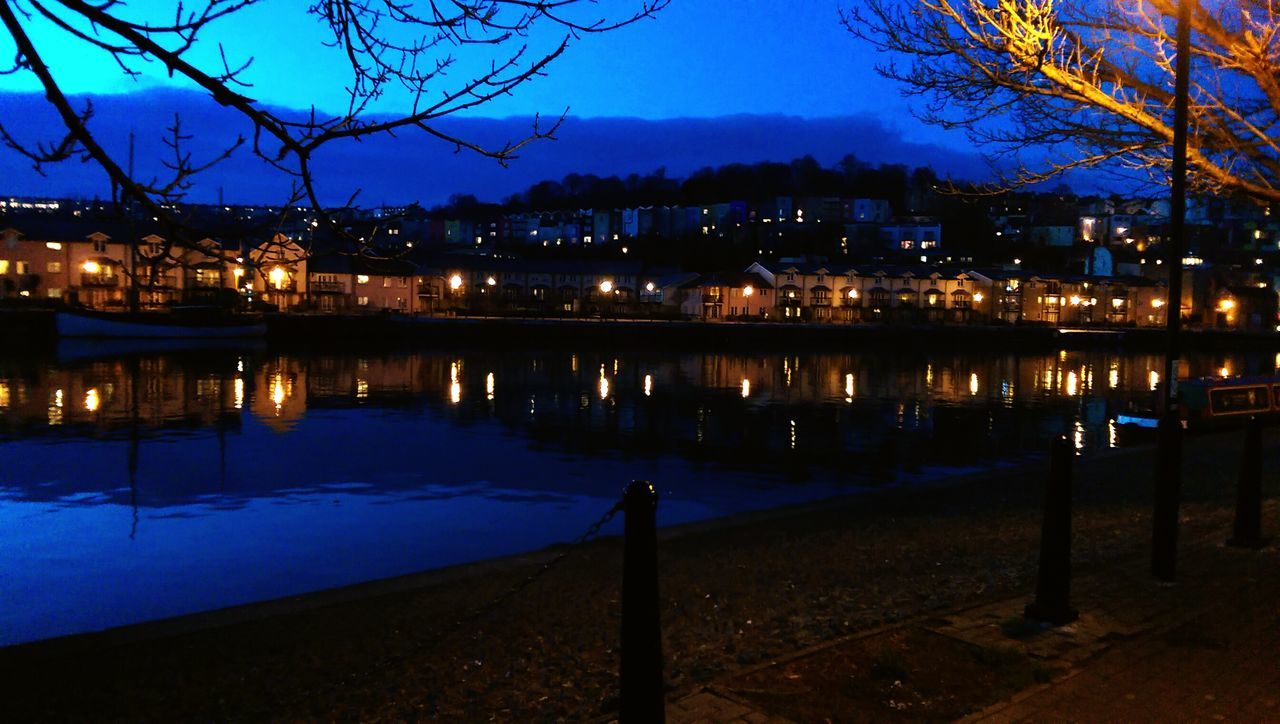 illuminated, night, architecture, built structure, building exterior, bare tree, sky, tree, outdoors, connection, reflection, clear sky, no people, blue, water, city, nature