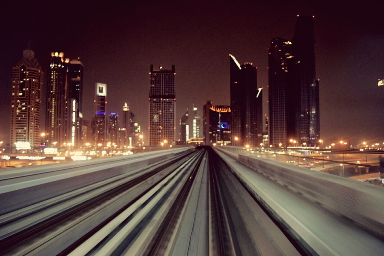 illuminated, night, architecture, building exterior, built structure, transportation, no people, city, railroad track, travel destinations, outdoors, skyscraper, high street, cityscape, sky
