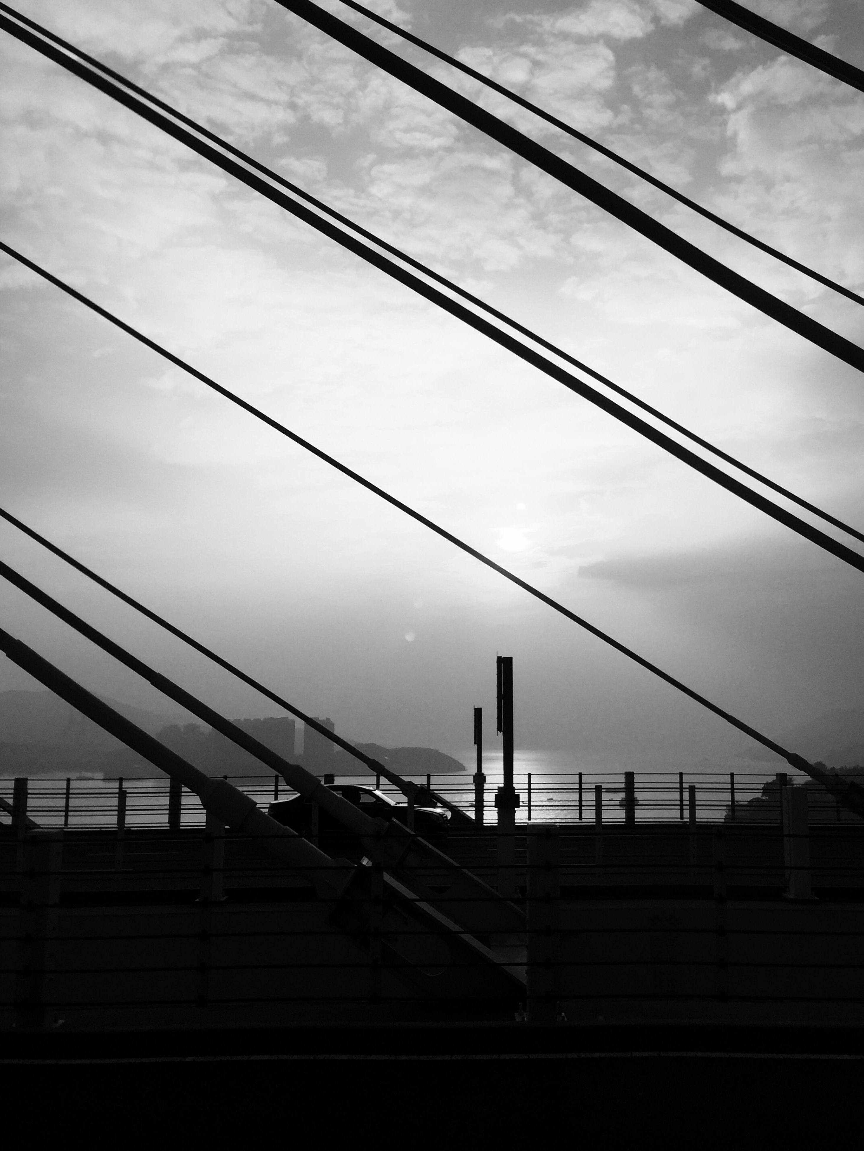 low angle view, connection, sky, power line, cable, silhouette, built structure, architecture, cloud - sky, electricity, power supply, electricity pylon, cloud, transportation, technology, power cable, bridge - man made structure, cloudy, dusk, railroad track