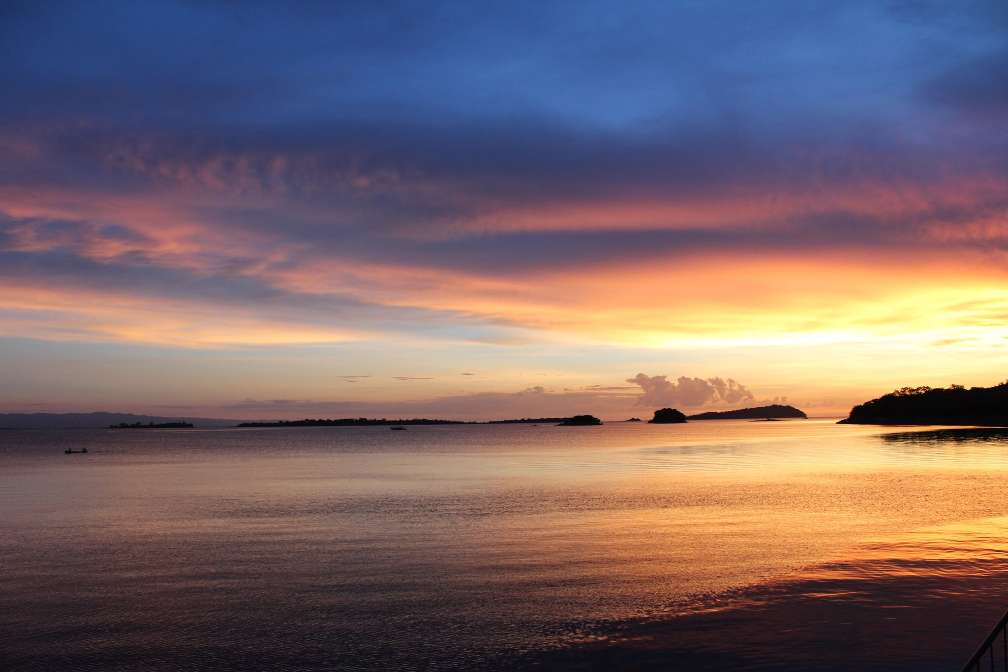 water, sunset, scenics, sea, tranquil scene, tranquility, beauty in nature, cloud - sky, sky, idyllic, calm, orange color, nature, cloud, majestic, dramatic sky, ocean, coastline, atmospheric mood, moody sky, non-urban scene, waterfront, shore, seascape, distant, outdoors, remote, atmosphere, cloudy, no people
