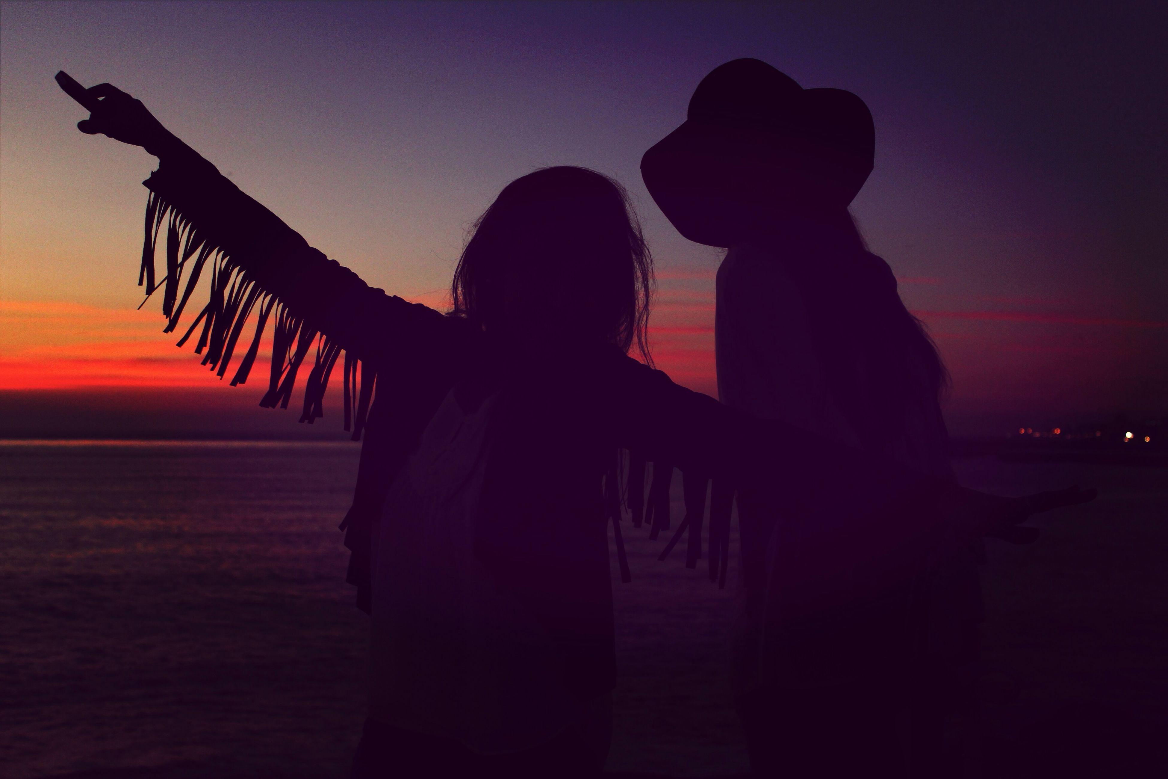sunset, silhouette, sky, lifestyles, leisure activity, men, sea, person, standing, dusk, rear view, water, orange color, travel, unrecognizable person, tourism, built structure