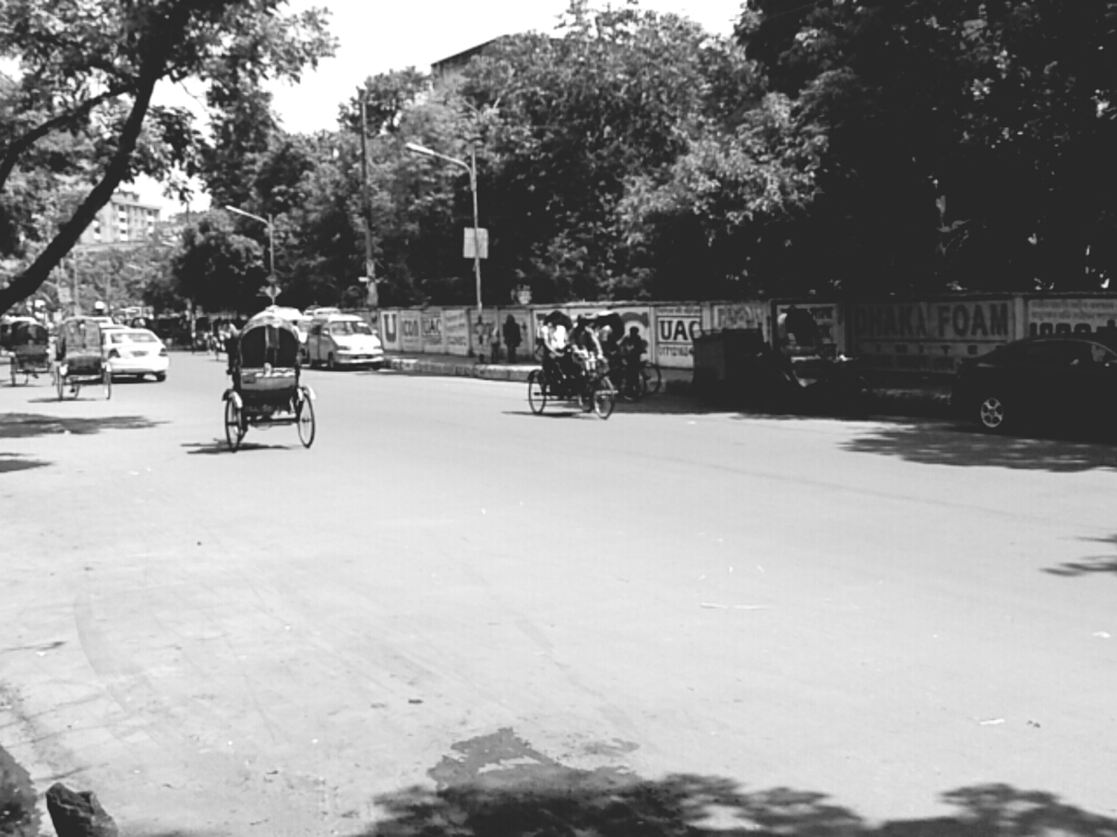 tree, men, transportation, street, lifestyles, land vehicle, leisure activity, building exterior, mode of transport, person, car, incidental people, day, shadow, road, sunlight, outdoors, built structure, travel