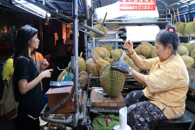Spotted In Thailand Durian Travel Photography Streetphotography Vendor Truck Asian Girl - a vendor offering a Durian Fruit to a Girl on Yaowarat Road in Chinatown Bangkok Thailand The Street Photographer - 2016 EyeEm Awards Street Food Worldwide Stinky Jackfruit Hate Or Love It Despicable Or Mouth Watering