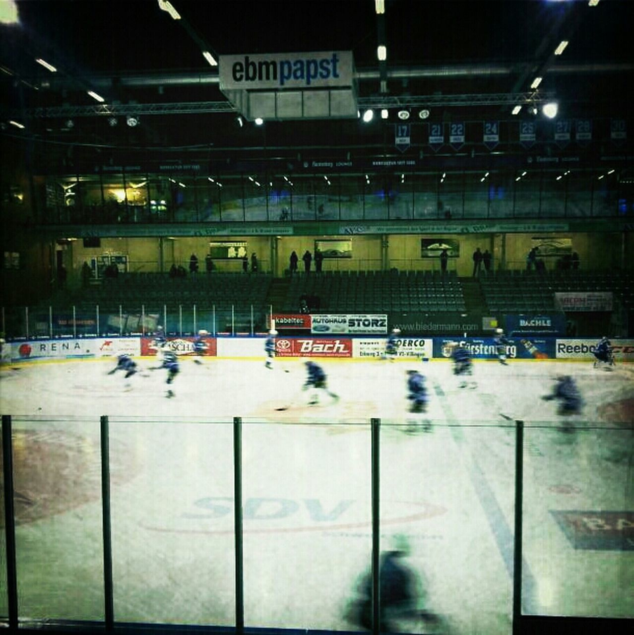 cold temperature, transportation, illuminated, indoors, winter, ice rink, large group of people, architecture, land vehicle, real people, snow, built structure, night, stadium, ice hockey, people