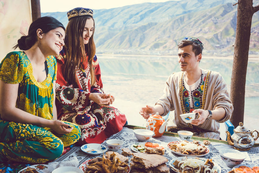 Three friends, people of Tajikistan, drinking tea and eating traditional Tajik food in front of a lake and the Pamir mountains Eating Friends Man Pamir Mountains Pamirs Sitting Tajik Cuisine Tajikistan Tea Woman Drinking Food Food And Drink Friendship Group Of People Smiling Table Tajik Togetherness Traditional Clothing Traditonal Women
