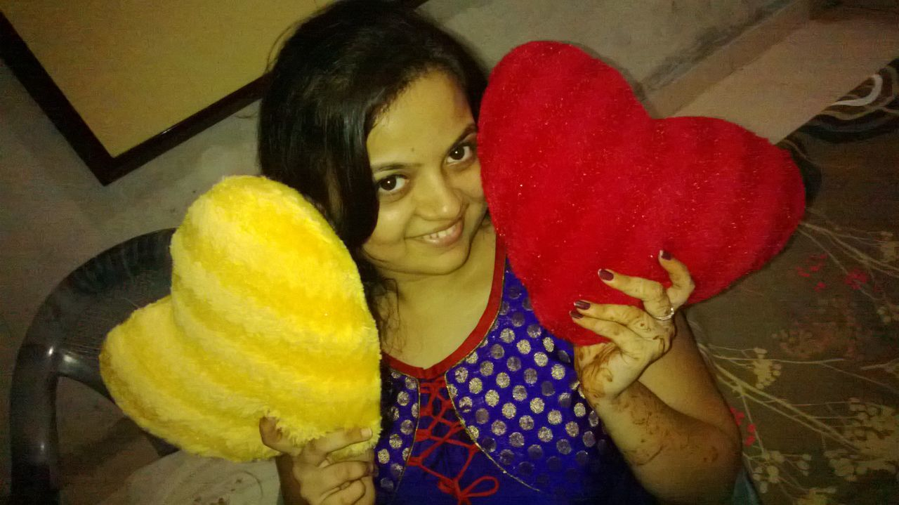 Indian Woman Holding Heart Shaped Cushions