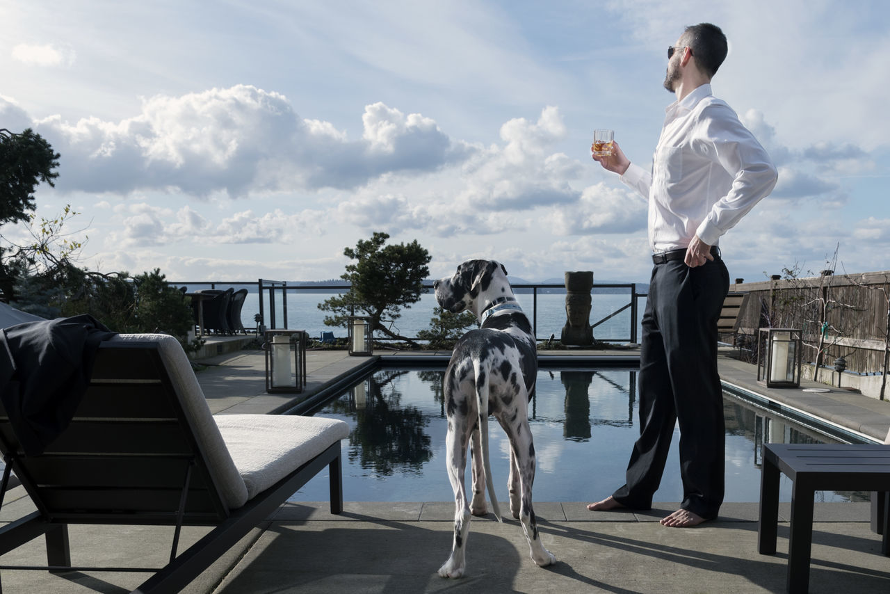 Wealthy man with drink and pet dog by the pool Adult Adults Only Attire Black And White Chairs Day Dog Formal Great Dane Handsome Harlequin Lounge Mature Adult Mature Men Men One Animal Outdoors People Pets Plant Pool Swimming Tall Twins Well-dressed