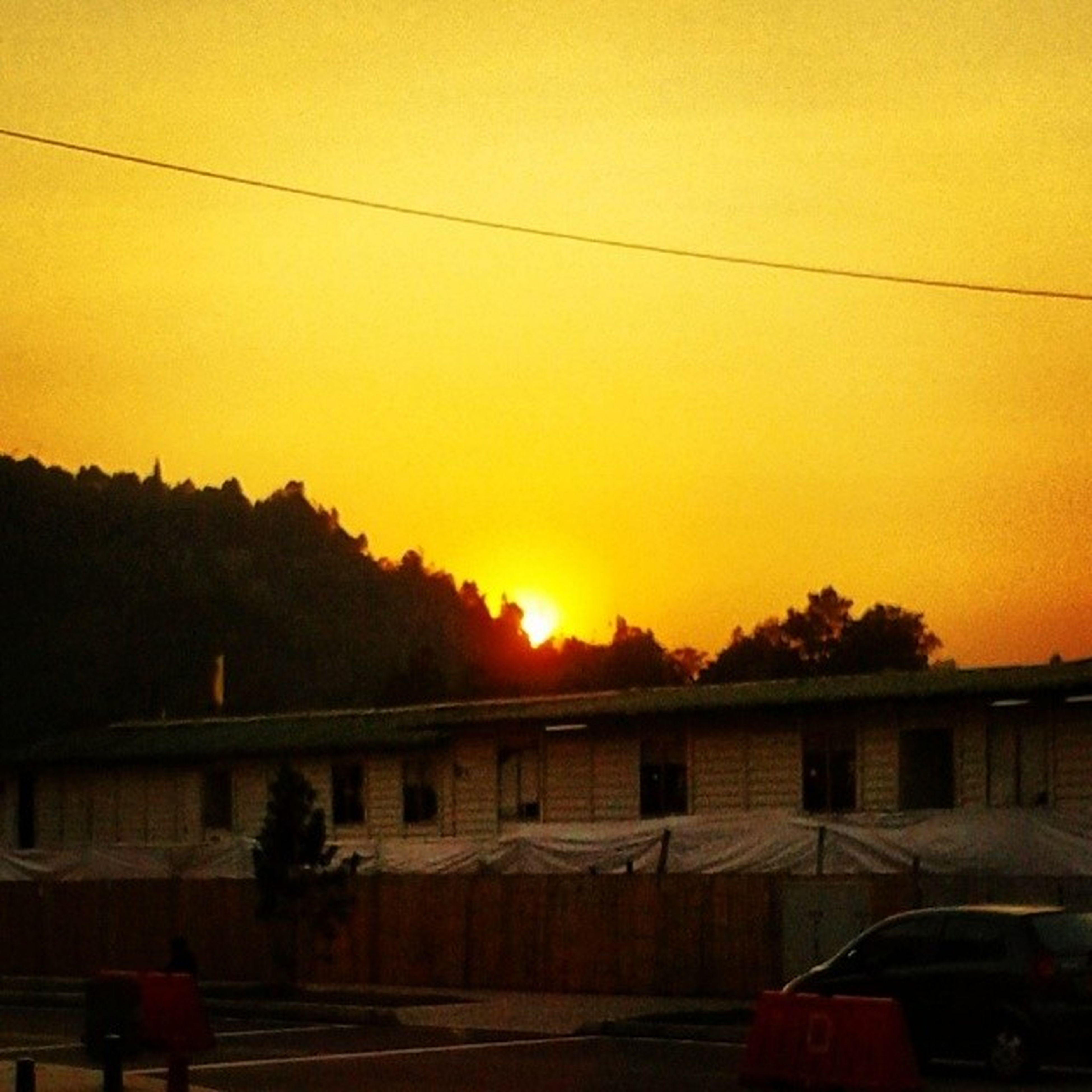 sunset, orange color, transportation, sky, mode of transport, land vehicle, building exterior, built structure, silhouette, architecture, tree, nature, beauty in nature, car, yellow, railing, scenics, outdoors, sun