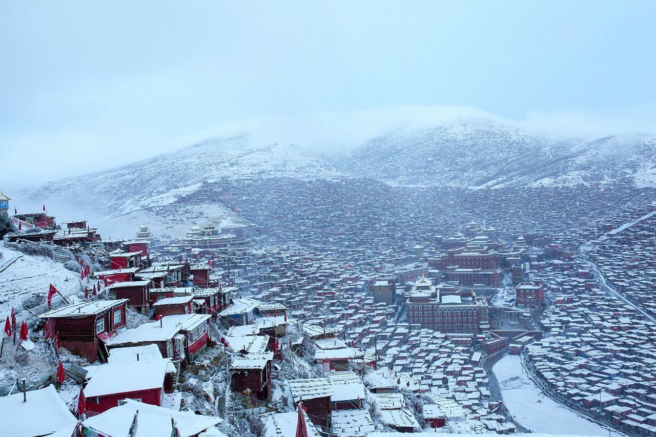 snow, winter, cold temperature, building exterior, architecture, built structure, mountain, high angle view, weather, outdoors, town, no people, residential building, house, nature, mountain range, day, sky, roof, scenics, beauty in nature, snowcapped mountain, cityscape
