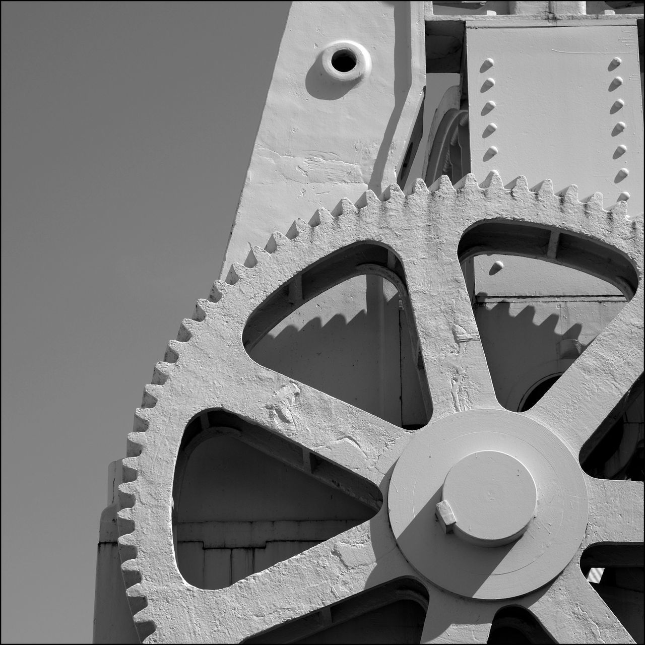 Low Angle View Of Metallic Gear Against Clear Sky