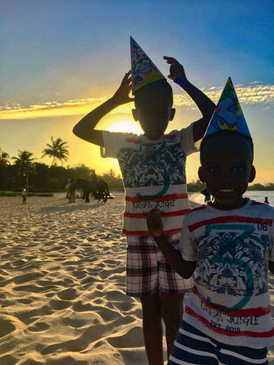 Beach Childhood Day Lifestyles Outdoors Real People Sand Sky Standing Sunlight Sunset Togetherness Two People Vacations