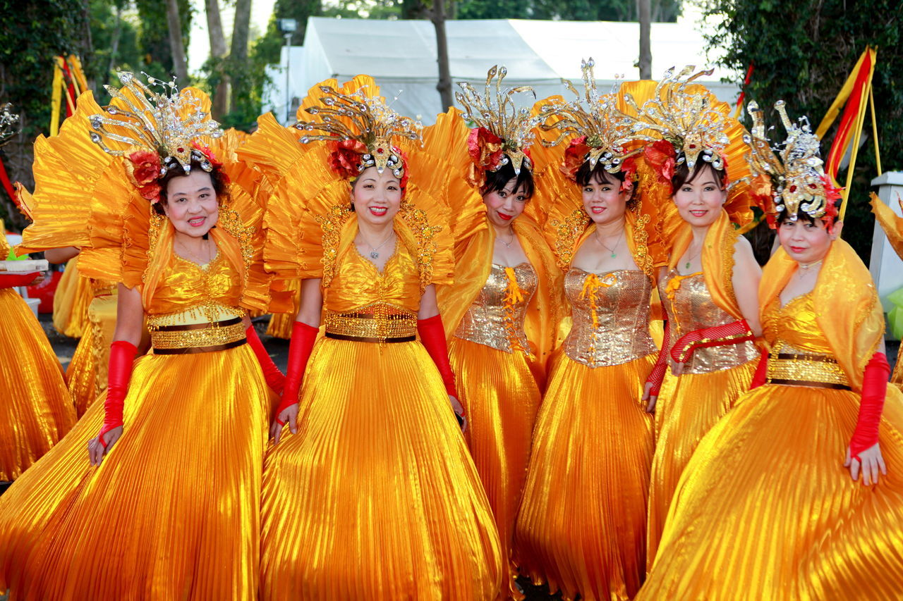 celebration, traditional festival, cultures, traditional clothing, real people, lifestyles, dancing, performance, costume, togetherness, yellow, day, tradition, front view, leisure activity, dancer, young women, traditional dancing, young adult, smiling, tree, outdoors, adult, people