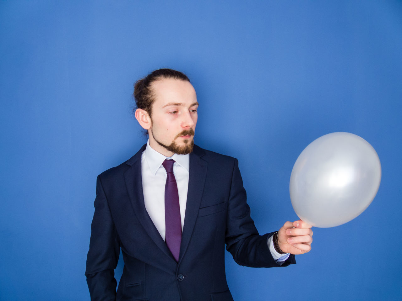 Young handsome bearded man in a suit looking at white balloon. Balloon Beard Blowing Up Balloon Blue Blue Background Business Business Finance And Industry Businessman Carefree Confidence  Economy Elegant Flower Helium Balloon Holding Man Manager One Person Party Person Relax Self Portrait Suit Well-dressed Young Adult