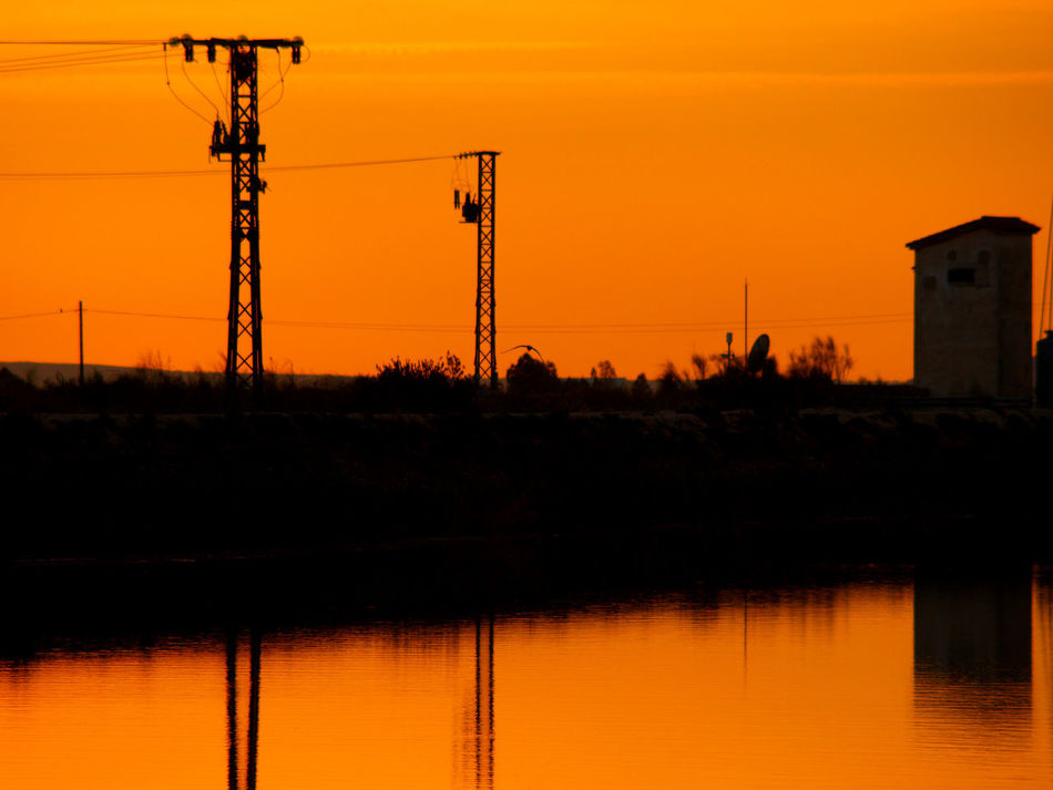 Beauty In Nature Electric Tower  Electricity  Electricity Pylon Energy Energy Tower Landscape Nature No People Orange Orange Color Outdoors Power Generation Power Line  Reflection Silhouette Silhouette Sky Sunset Sunset Silhouettes Sunset_collection Tranquility Warm Colors Water Water Reflections