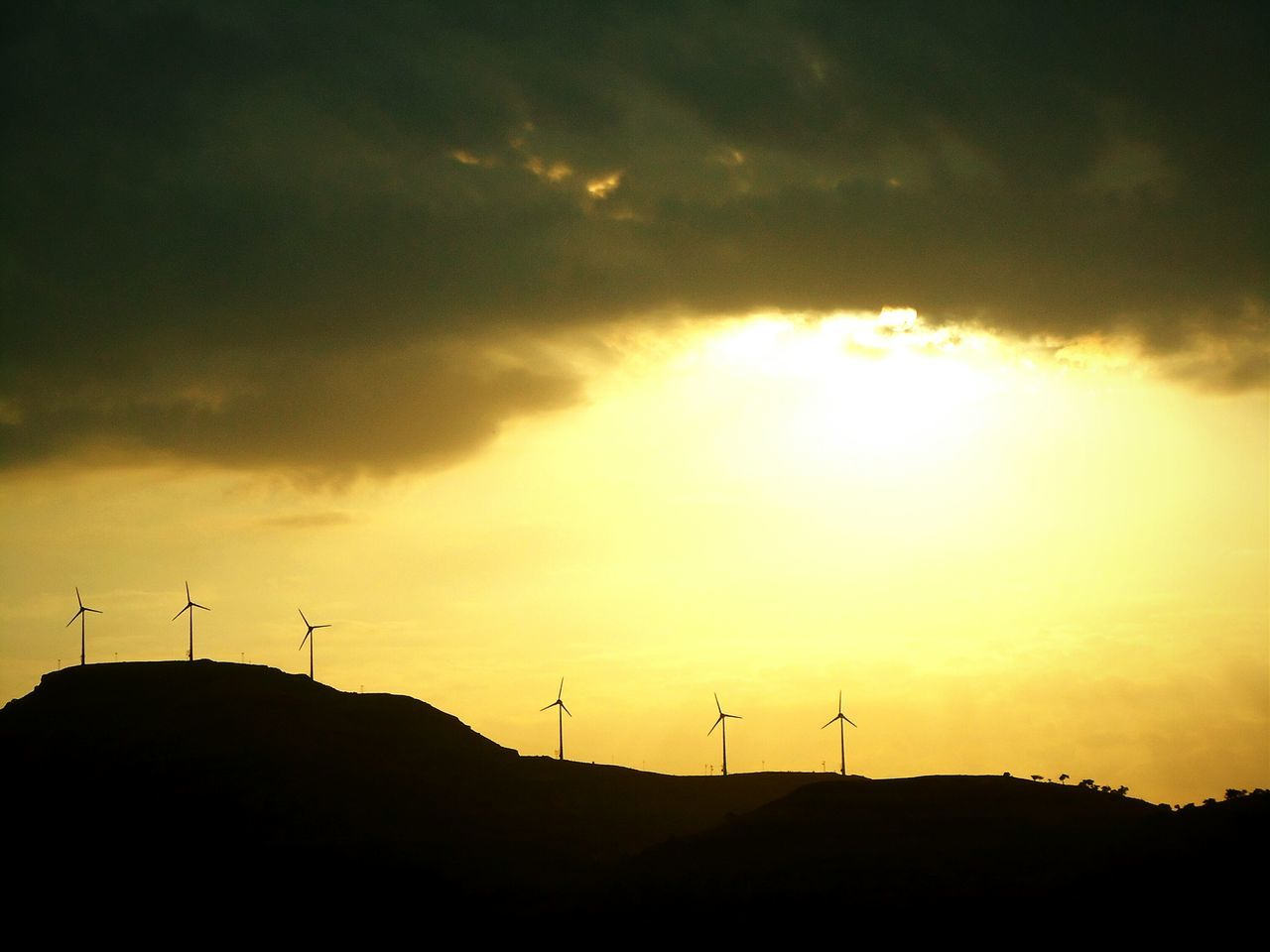 Silhouette Windmills On Field Against Cloudy Sky During Sunset