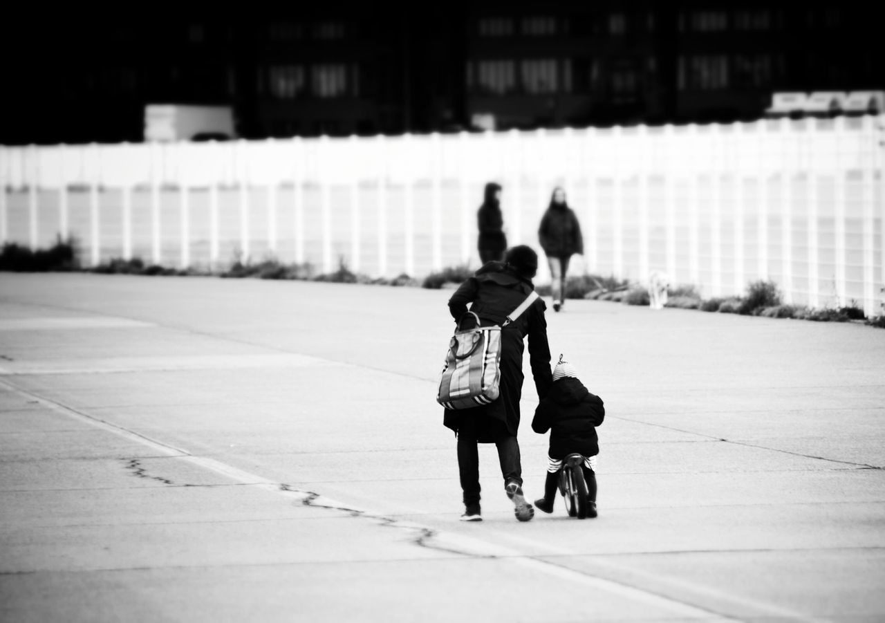 Full Length Rear View Of Mother Teaching Daughter Bicycle On Street