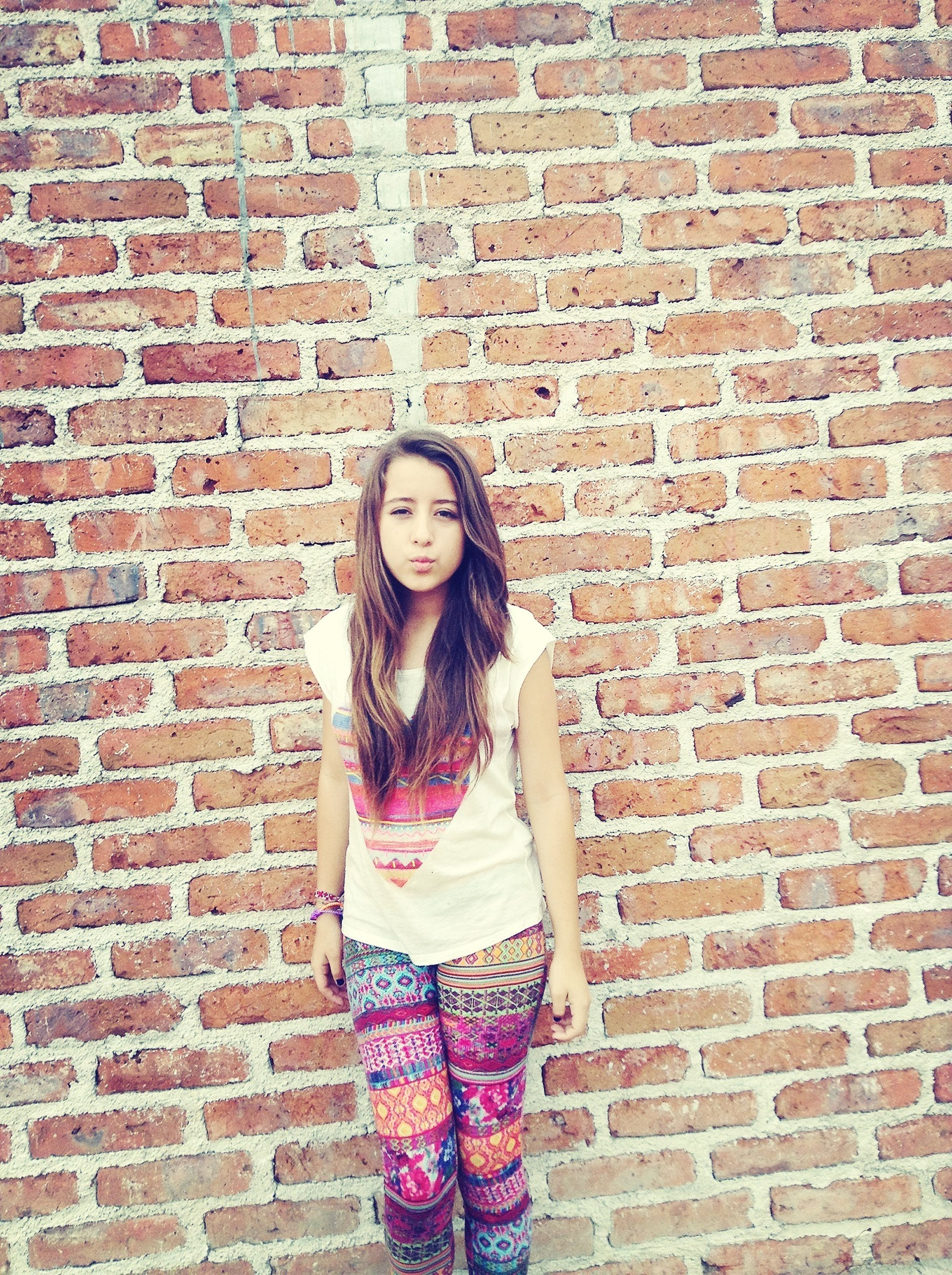young adult, portrait, young women, person, looking at camera, lifestyles, front view, brick wall, standing, casual clothing, long hair, smiling, wall - building feature, leisure activity, three quarter length, happiness, red